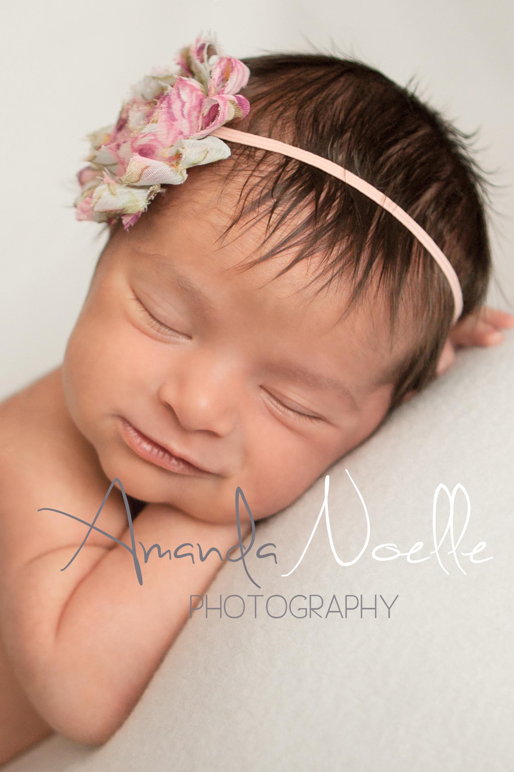 Newborn baby girl sleeping smile with shabby chic pinkheadband on white fabric backdrop, beanbag pose, Westchester, County New York Newborn Photographer, Amanda Noelle Photography.