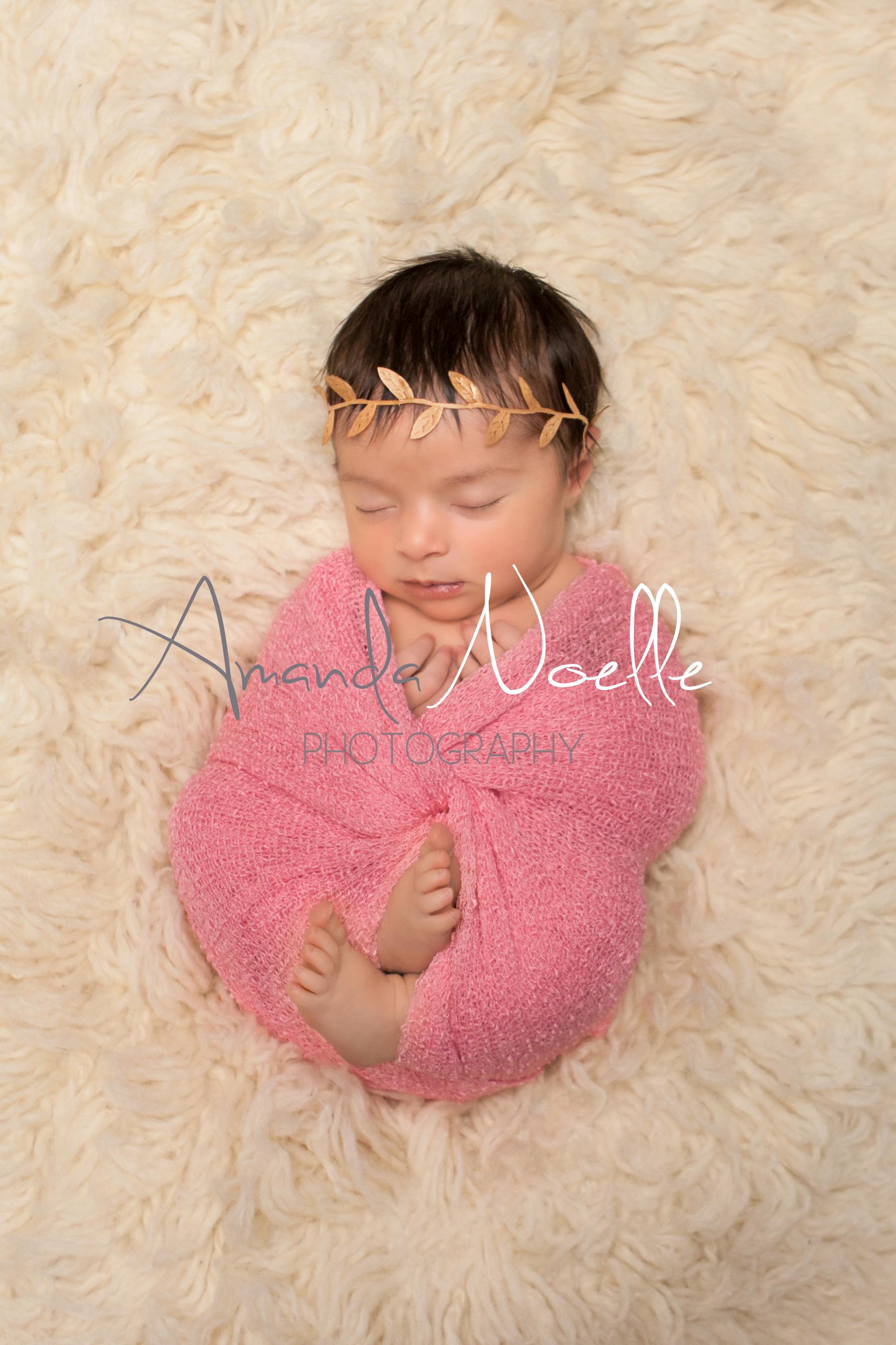 Newborn baby girl sleeping with gold leaf  headband wrapped in stretch knit pink wrap on cream creme flokati rug, Westchester, County New York Newborn Photographer, Amanda Noelle Photography.