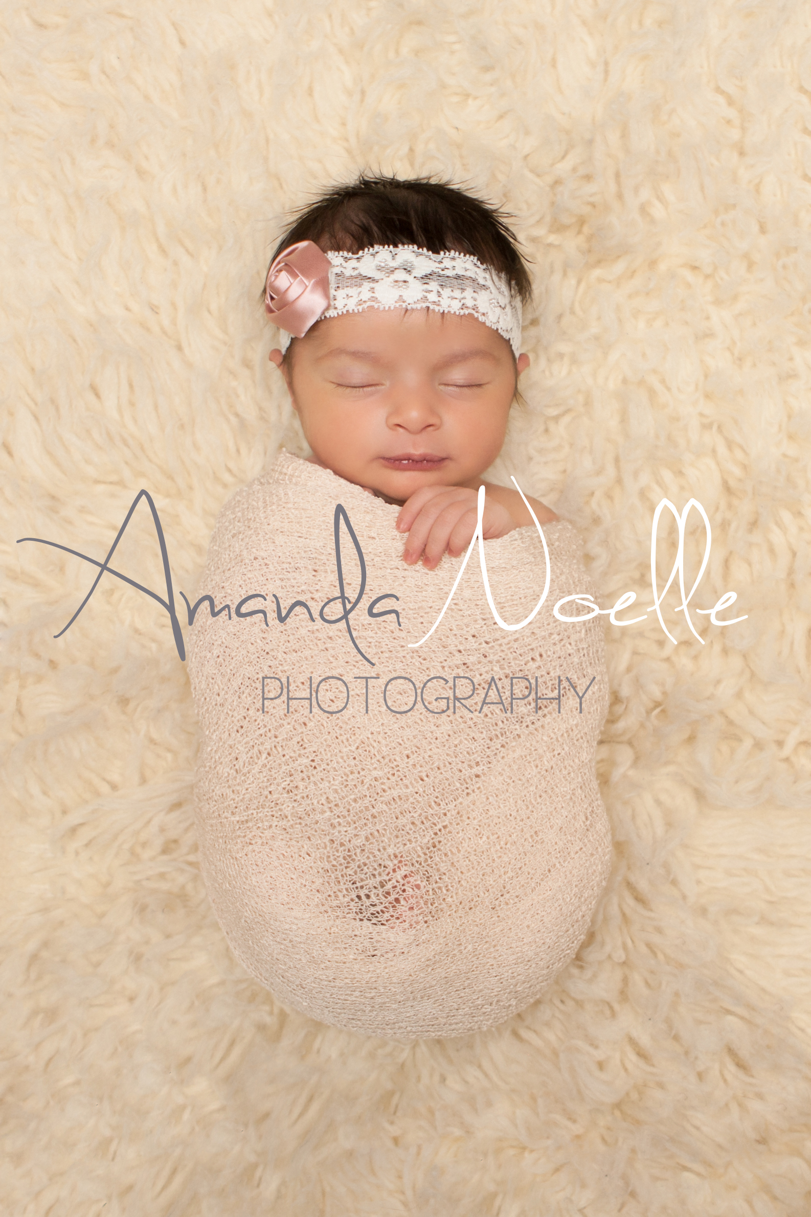 Newborn baby girl sleeping with pink and white lace rose flower  headband wrapped in stretch knit cream wrap on cream creme flokati rug, Westchester, County New York Newborn Photographer, Amanda Noelle Photography.