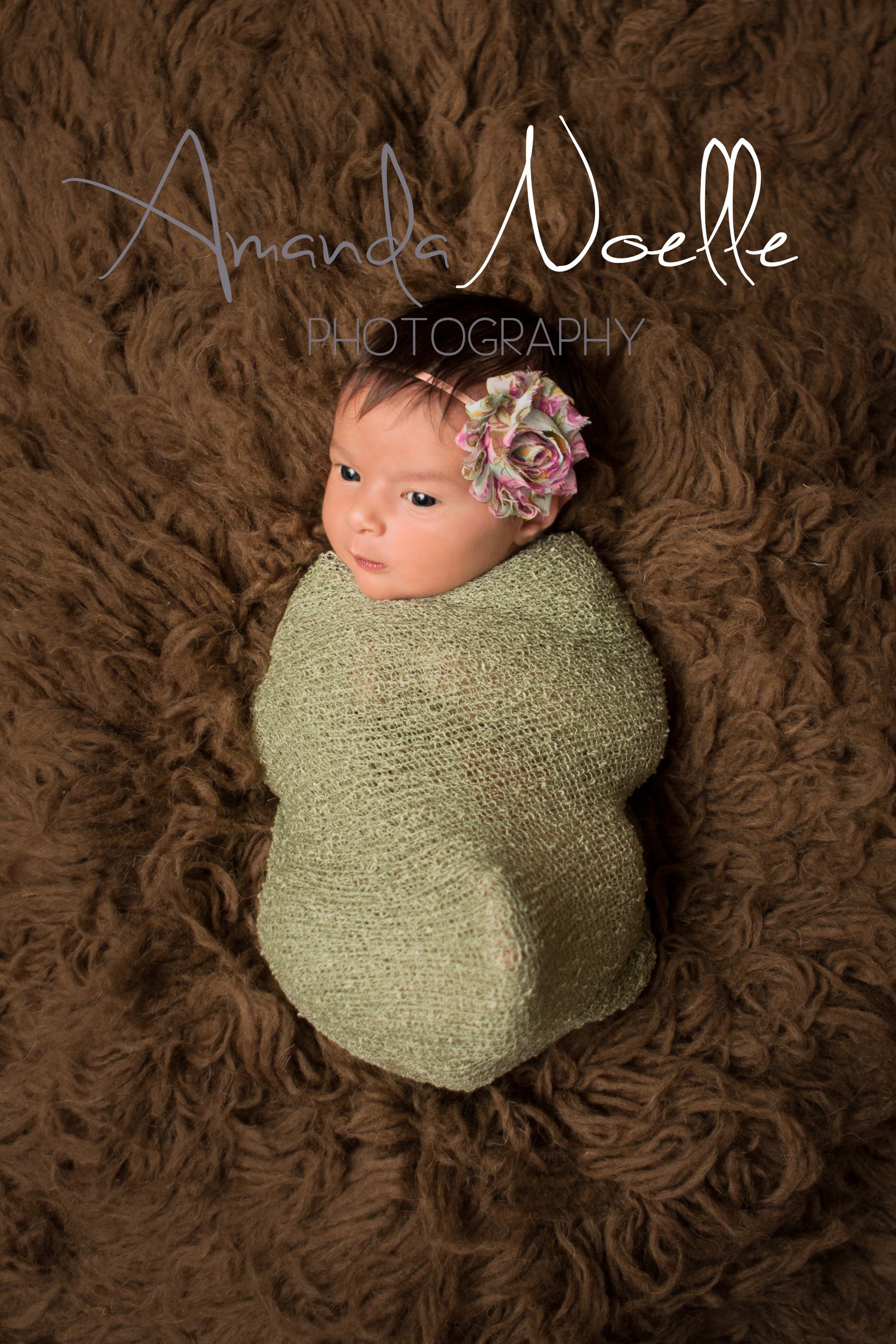 Newborn baby girl awake with pink and green shabby chic flower   headband wrapped in stretch knit green wrap on brown flokati rug, Westchester, County New York Newborn Photographer, Amanda Noelle Photography.