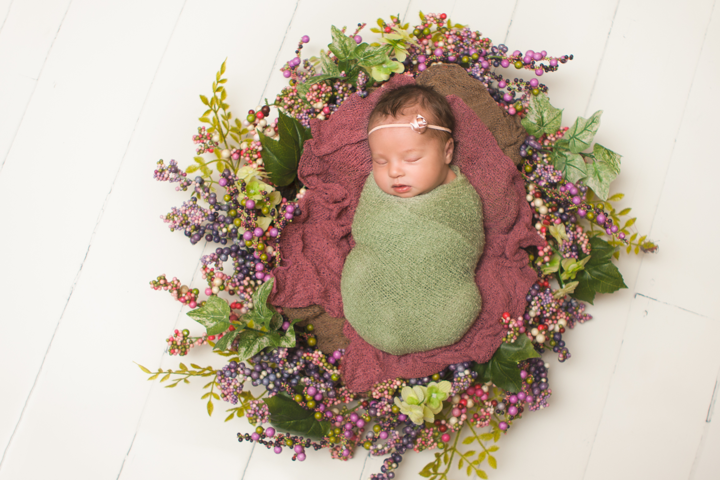 Newborn baby girl sleepingspring photos, wrapped in green knit stretch wrap, spring wreath, white wood floor backdrop.