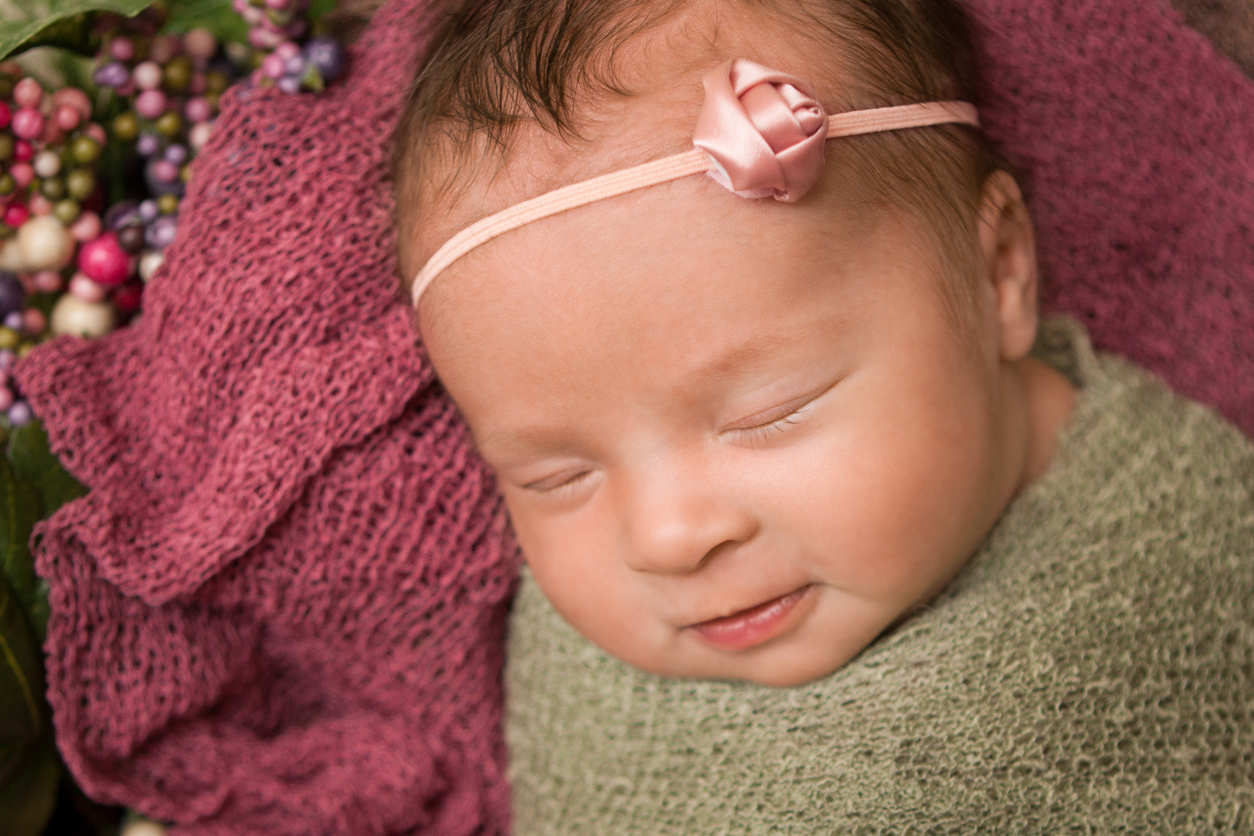 Newborn baby girl sleeping  smile spring photos, wrapped in green knit stretch wrap, spring wreath, white wood floor backdrop.
