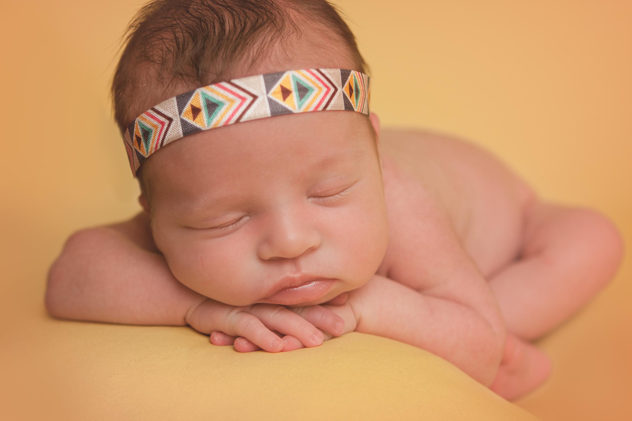 Newborn baby girl sleeping pose, bohemian headband, yellow blanket fabric backdrop, head chin on hands bean bag pose.