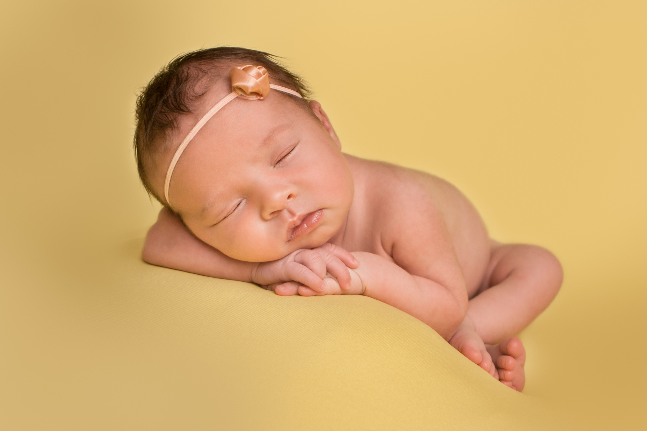 Newborn baby girl sleeping pose, rose pink flower headband, yellow blanket fabric backdrop, head chin on hands bean bag pose.