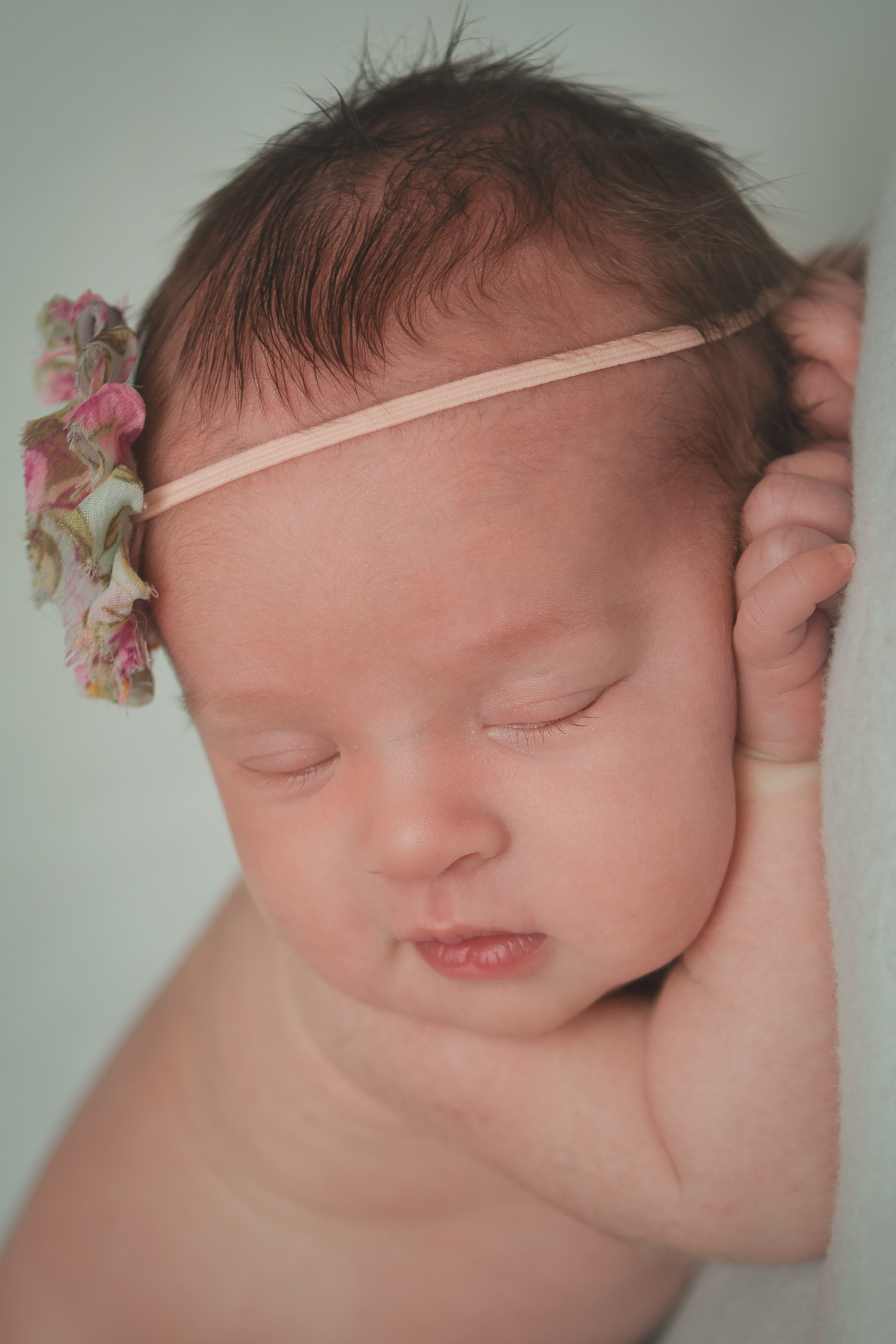 Newborn baby girl sleeping pose, rose pink flower headband, green blue blanket fabric backdrop, head chin on hands bean bag pose.