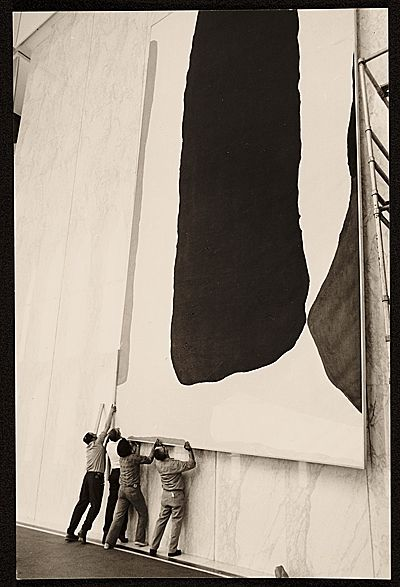A crew installing Helen Frankenthaler's painting 'Guiding Red', 1977