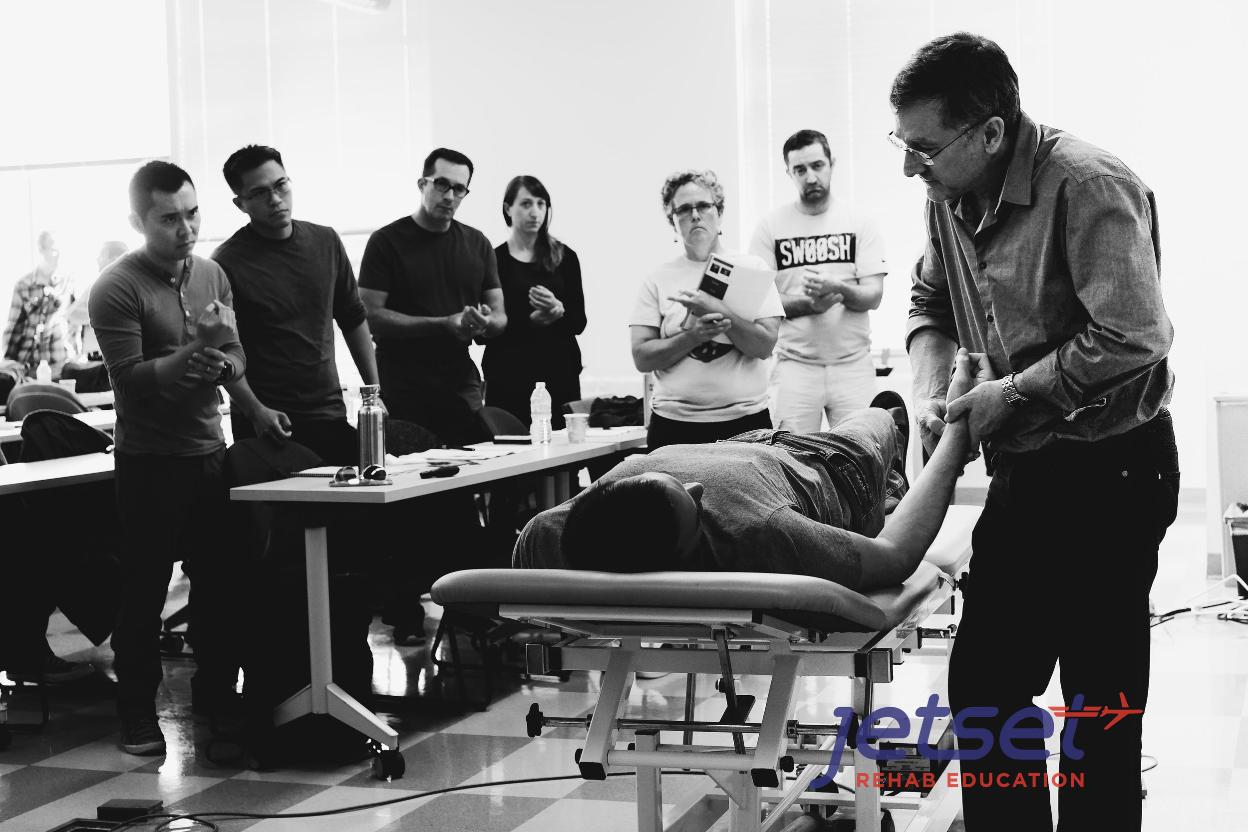 Michael Shacklock demonstrates the palpation of the   Median Nerve   as students look on.