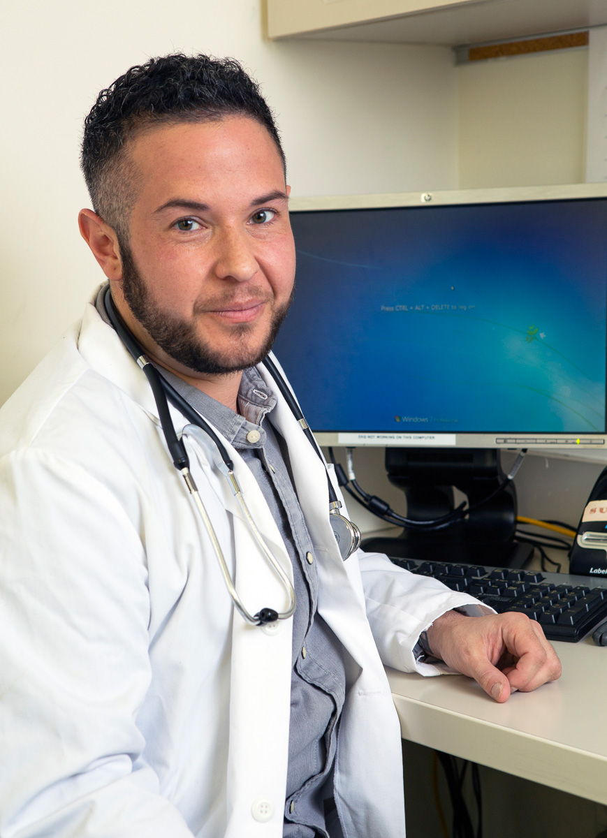 A transmasculine doctor in front of his computer.jpg