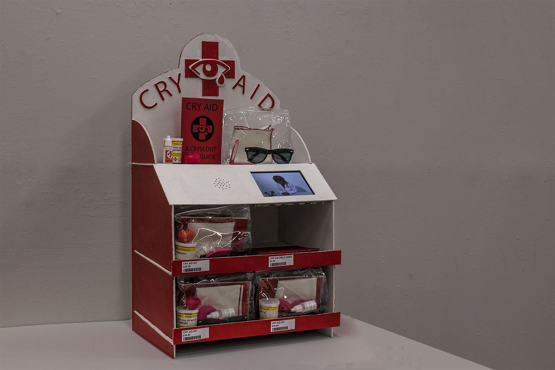 "Cry Aid Display    8 min looping infomercial, Cry Aid Kits, Cry Aid Field Guides, wooden display, price tags  32"" x 19"" x 13""  2017."