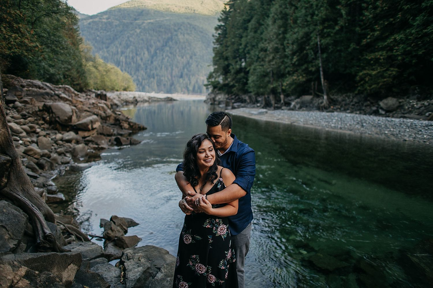 Copy of couple hugging candid moment water trees mountain