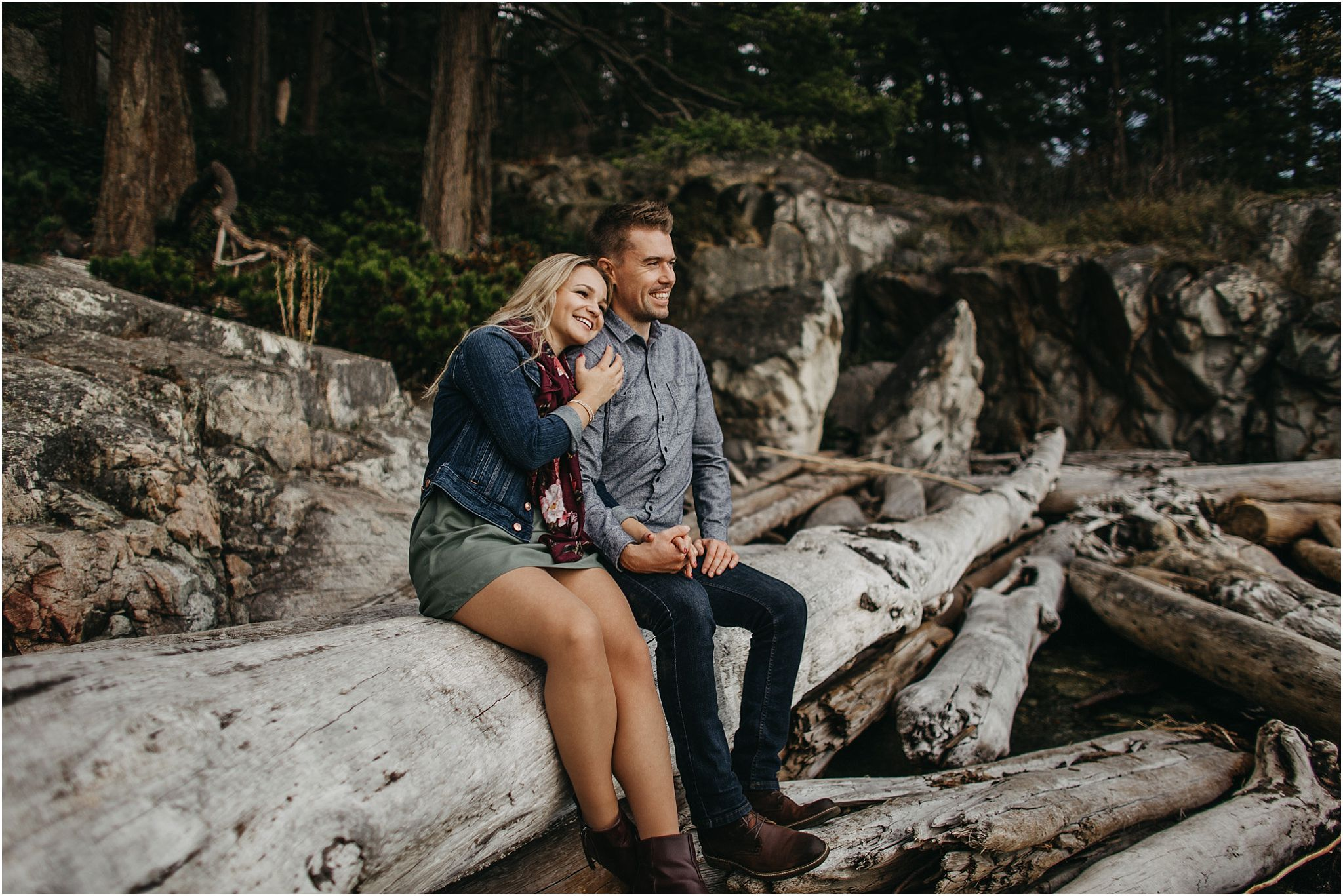 couple sitting on log at lighthouse park looking out at view