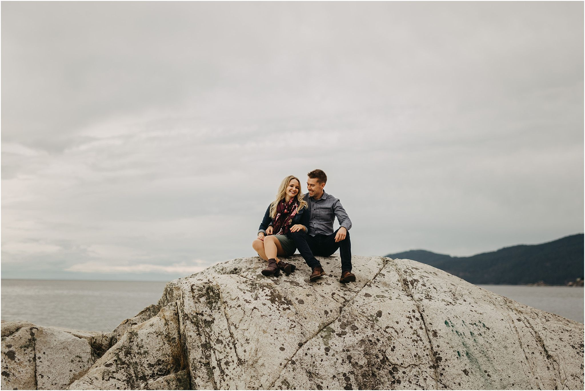 couple sitting on rock by ocean at lighthouse park