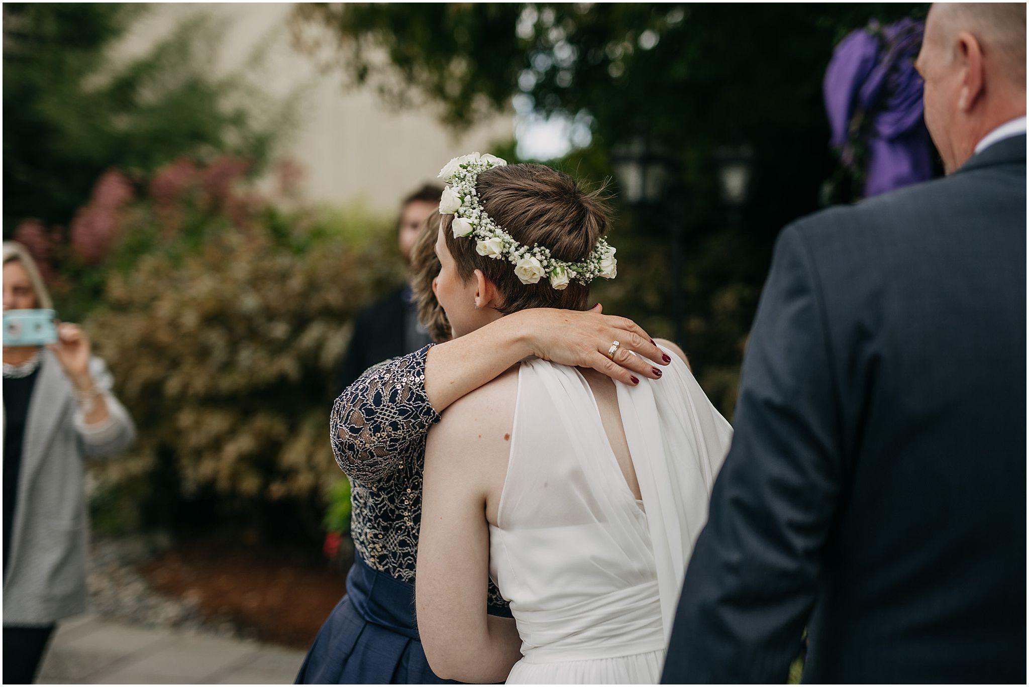 mother of bride hugging bride at ceremony