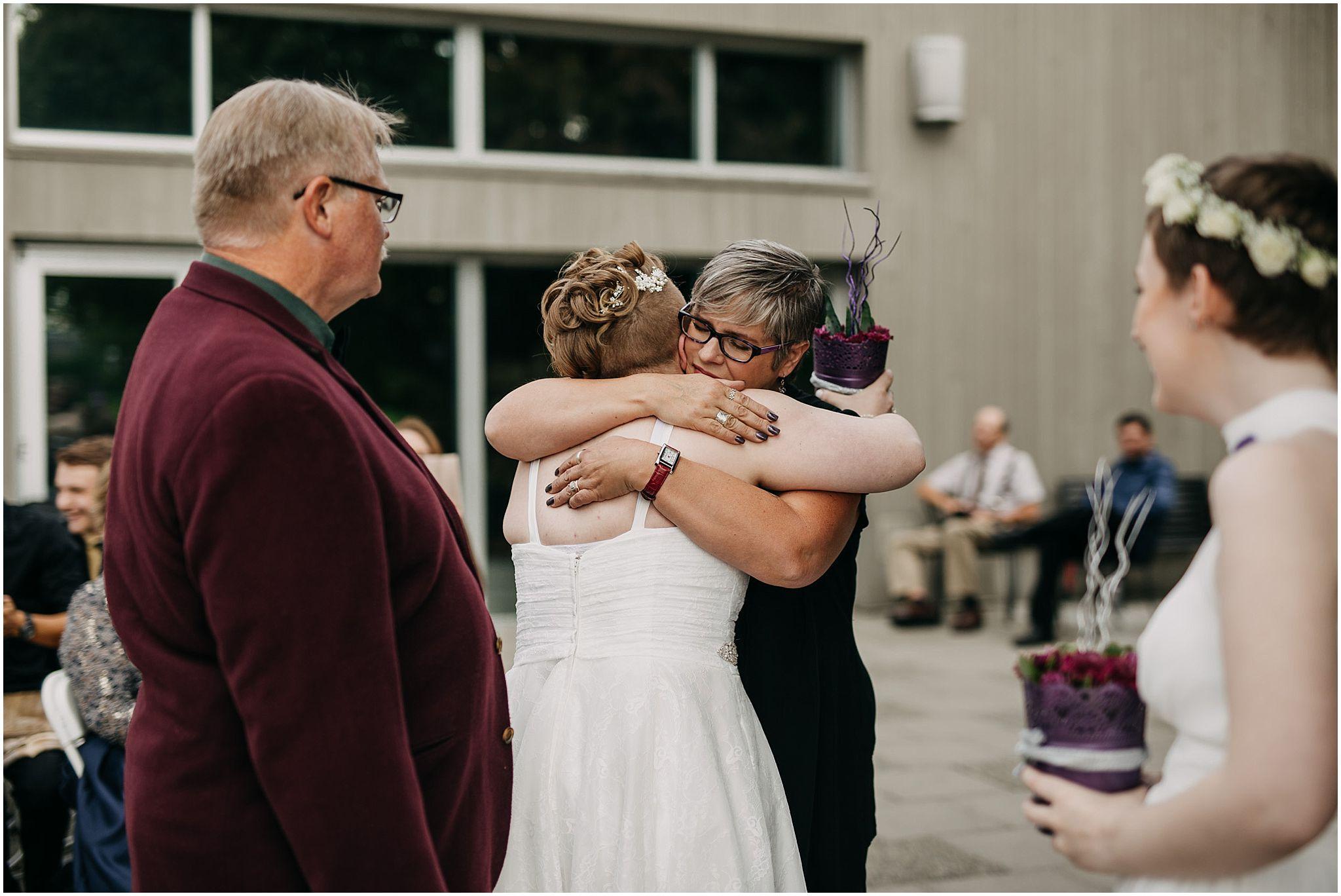 mother of bride hugging bride wedding ceremony