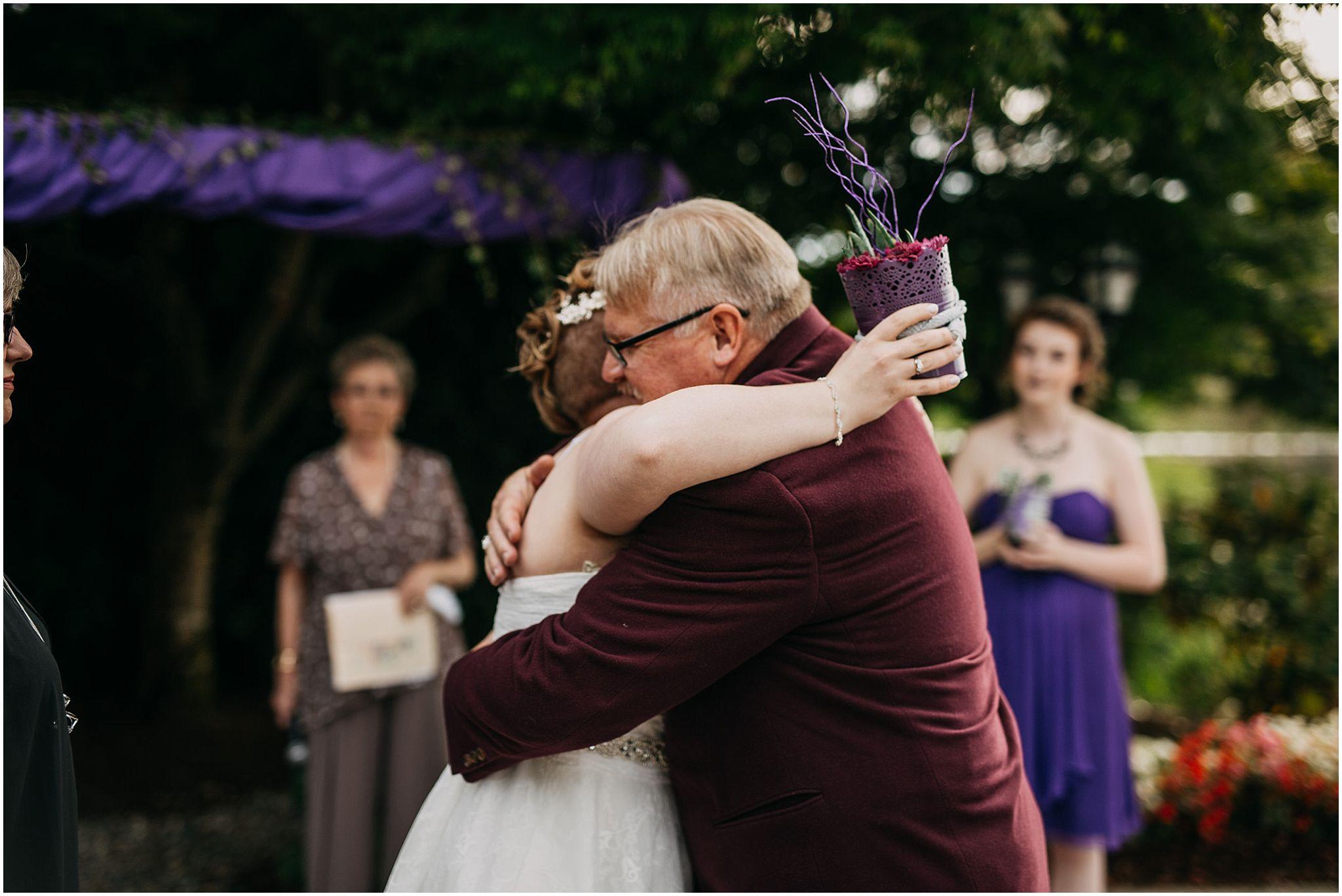 father of bride hugging bride wedding ceremony