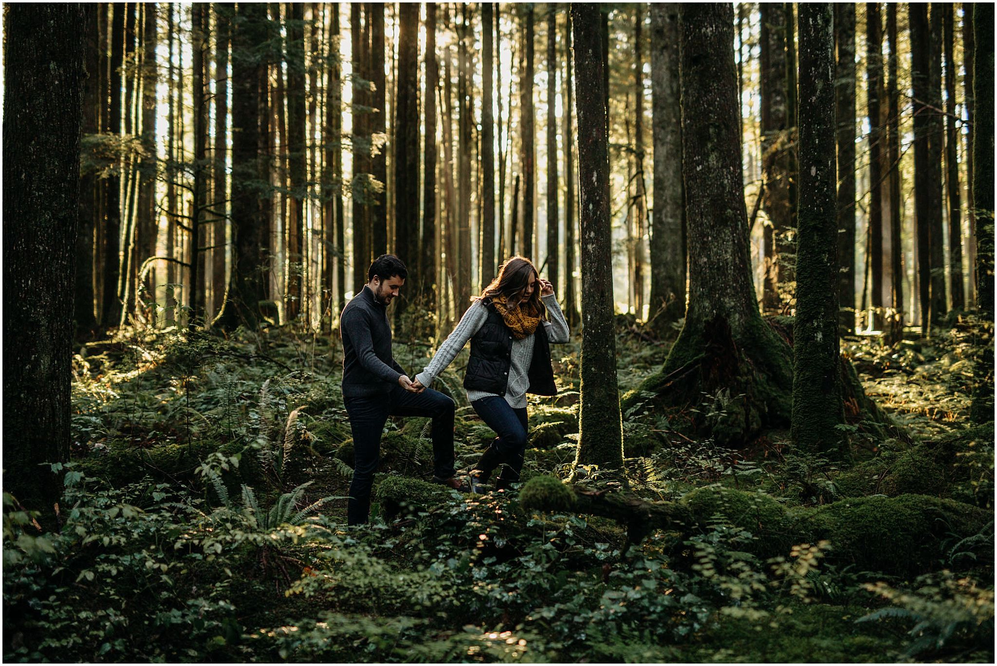 girl leading guy out of forest engagement photos