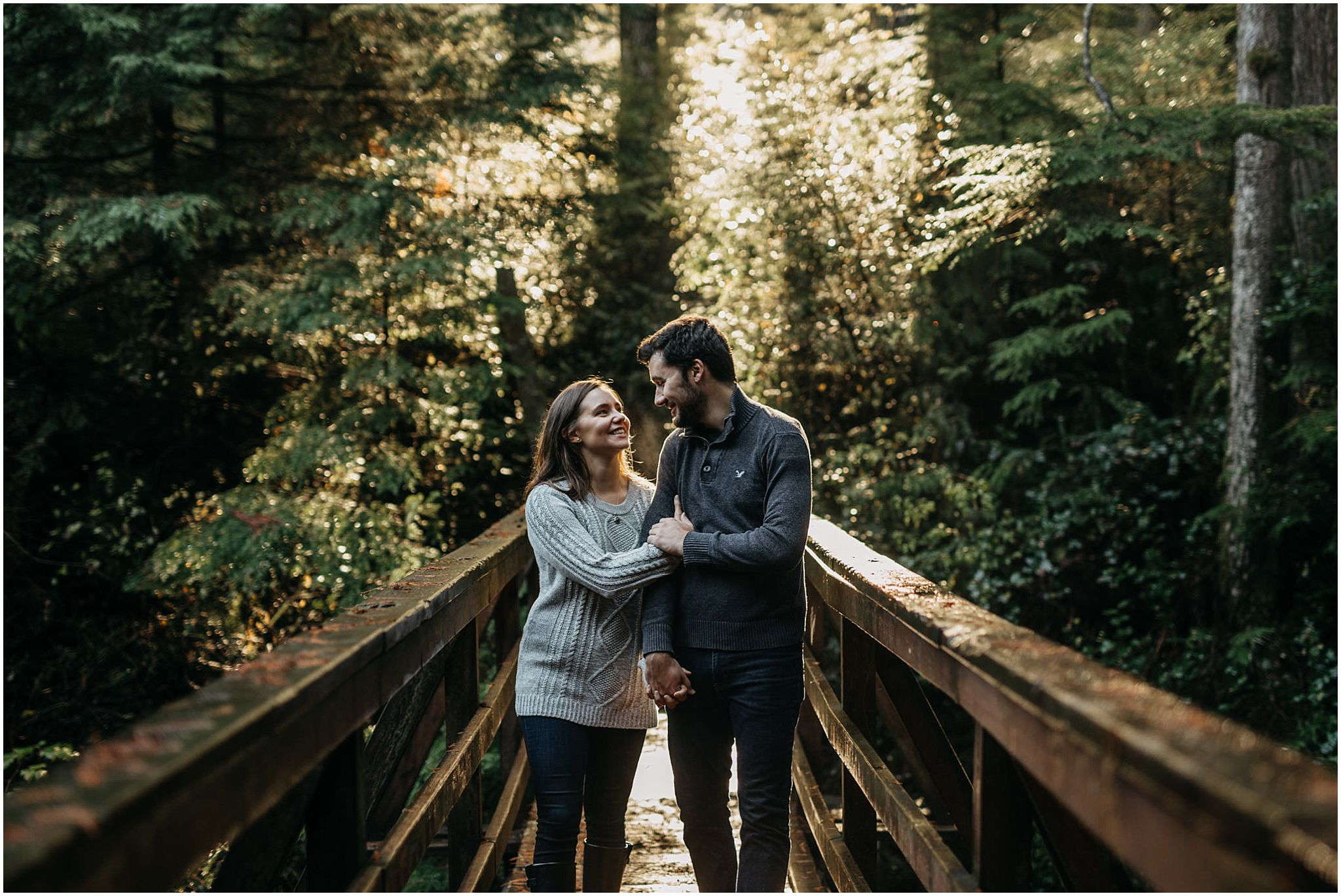 couple walking on bridge sun shining through trees rolley lake engagement