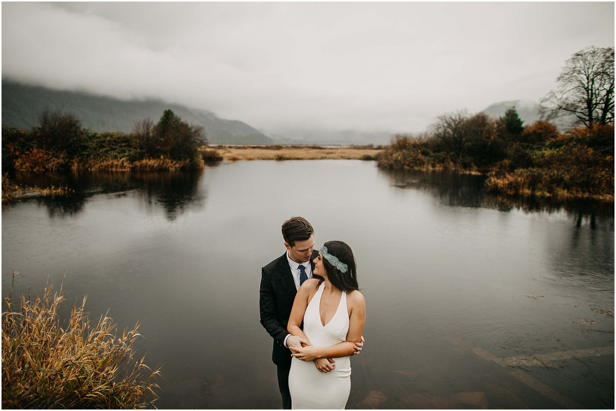 couple standing in front of pitt lake reflection fog