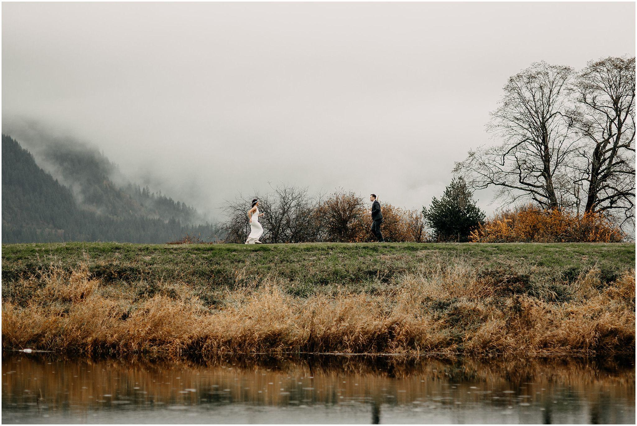 couple running towards each other pitt lake marsh engagement