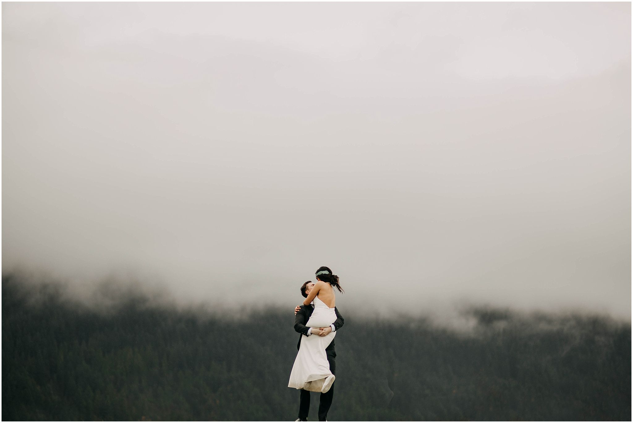 couple spinning around foggy cloudy minimal pitt lake engagement