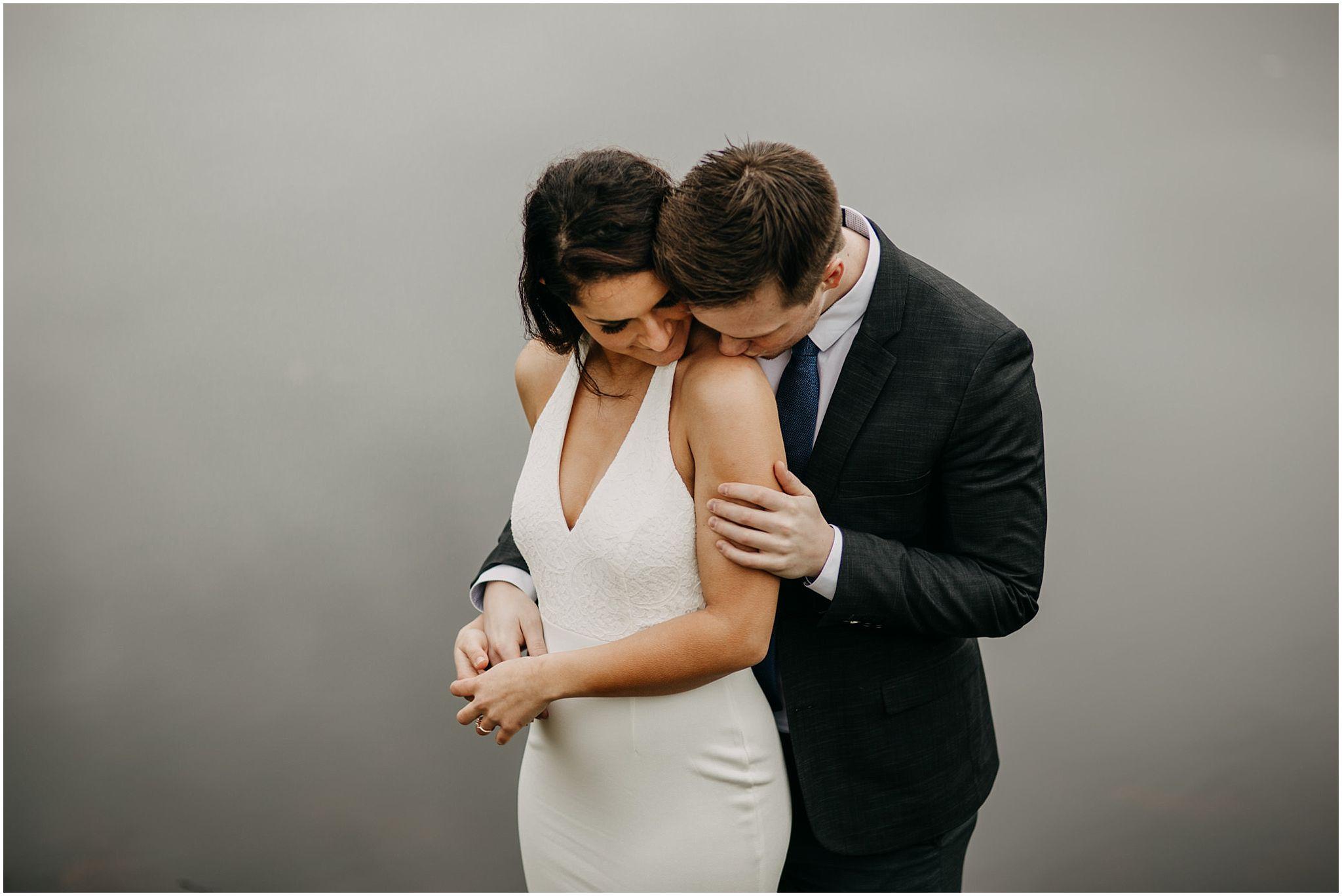 guy kissing girl's shoulder intimate moment pitt lake engagement