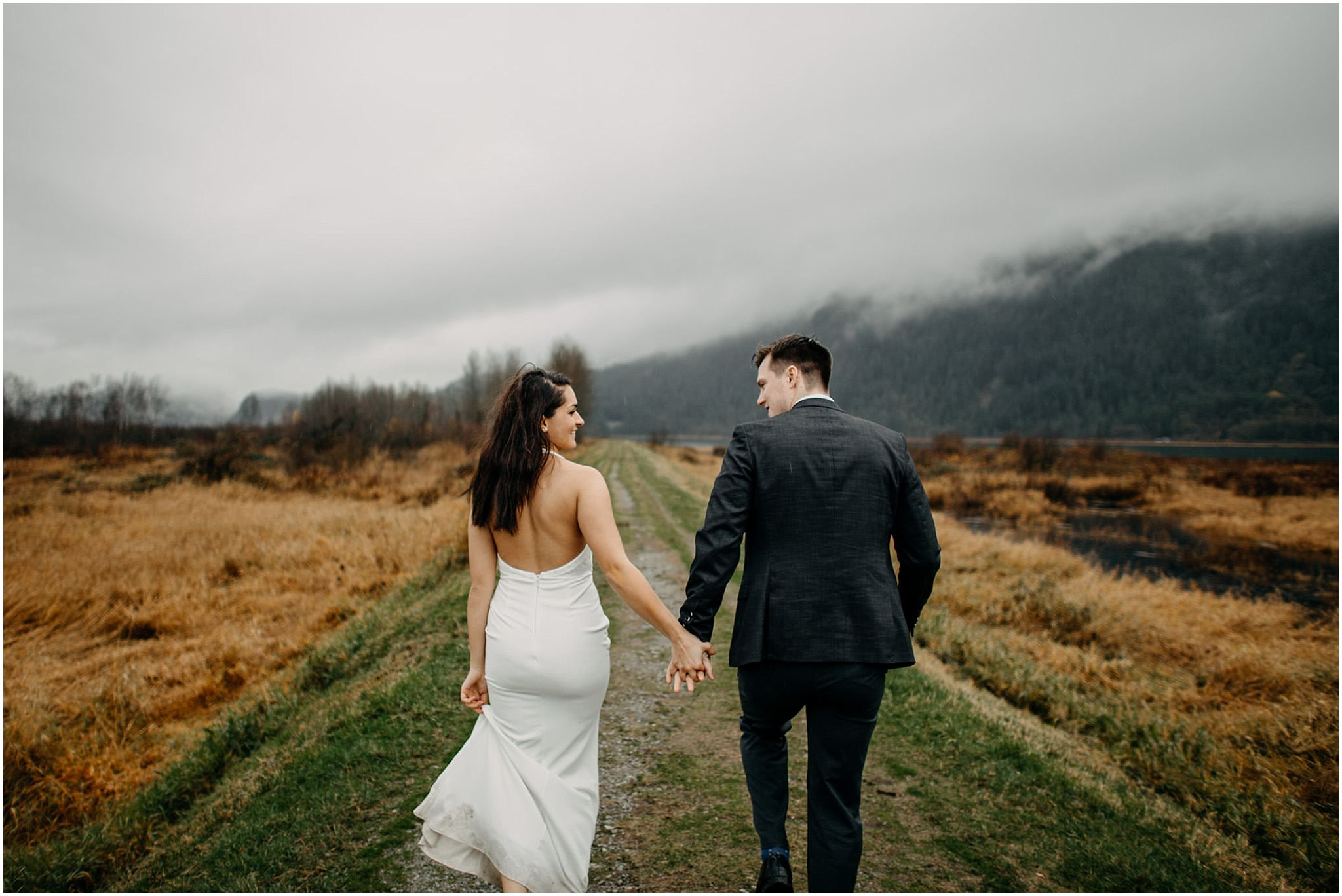 couple holding hands walking along pitt lake marsh engagement photos