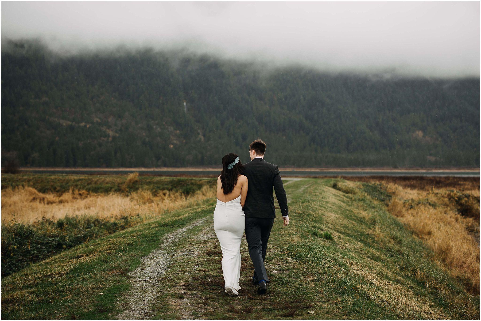 couple walking away pitt lake marsh pnw engagement