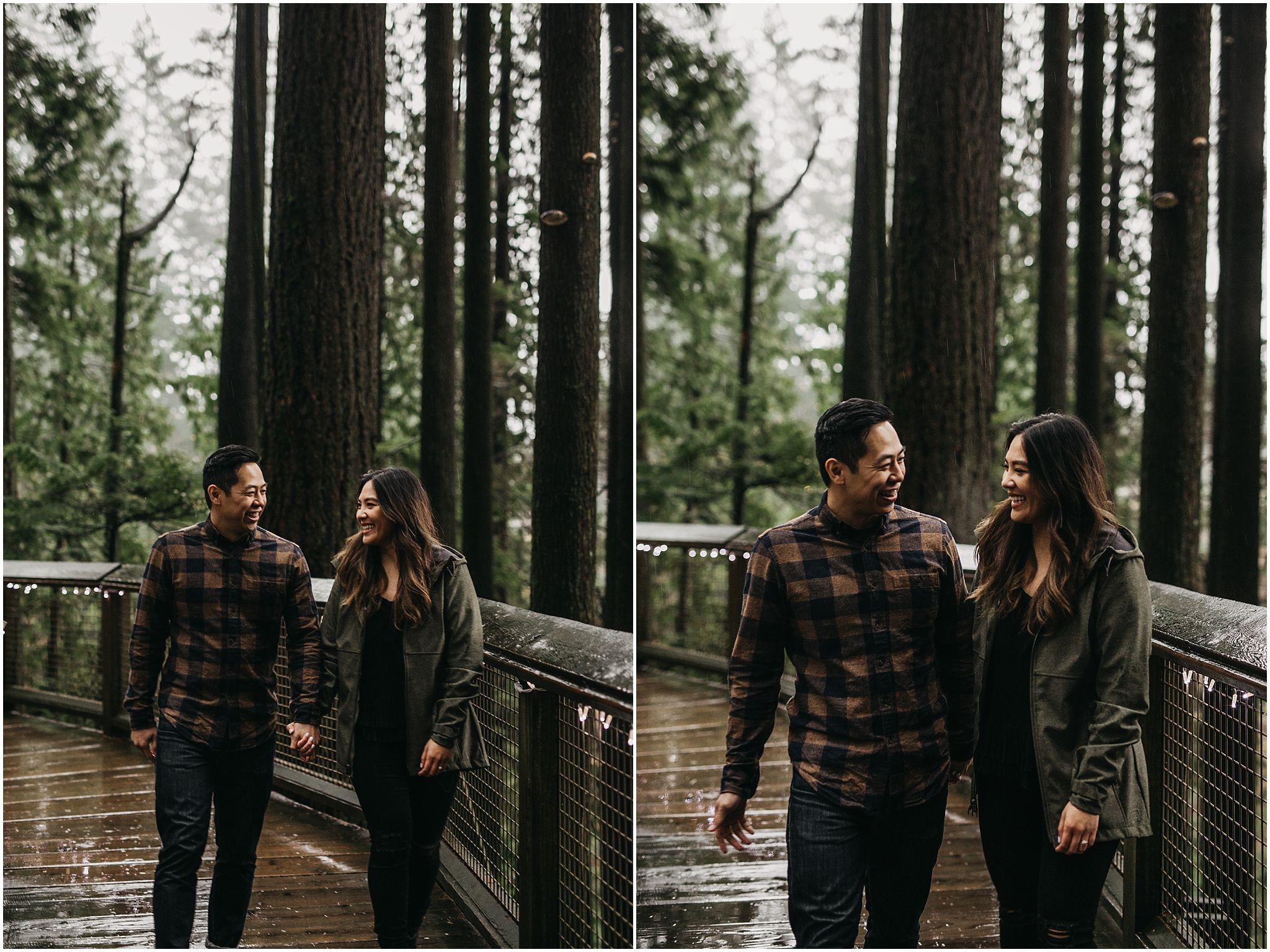 couple walking holding hands through capilano suspension bridge park engagement