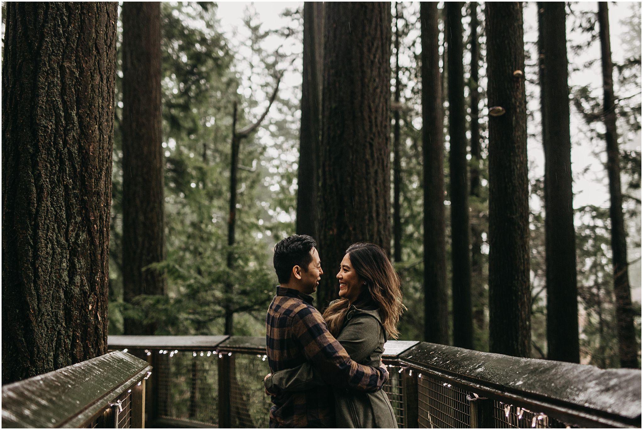 engaged couple capilano suspension bridge nature walk trees