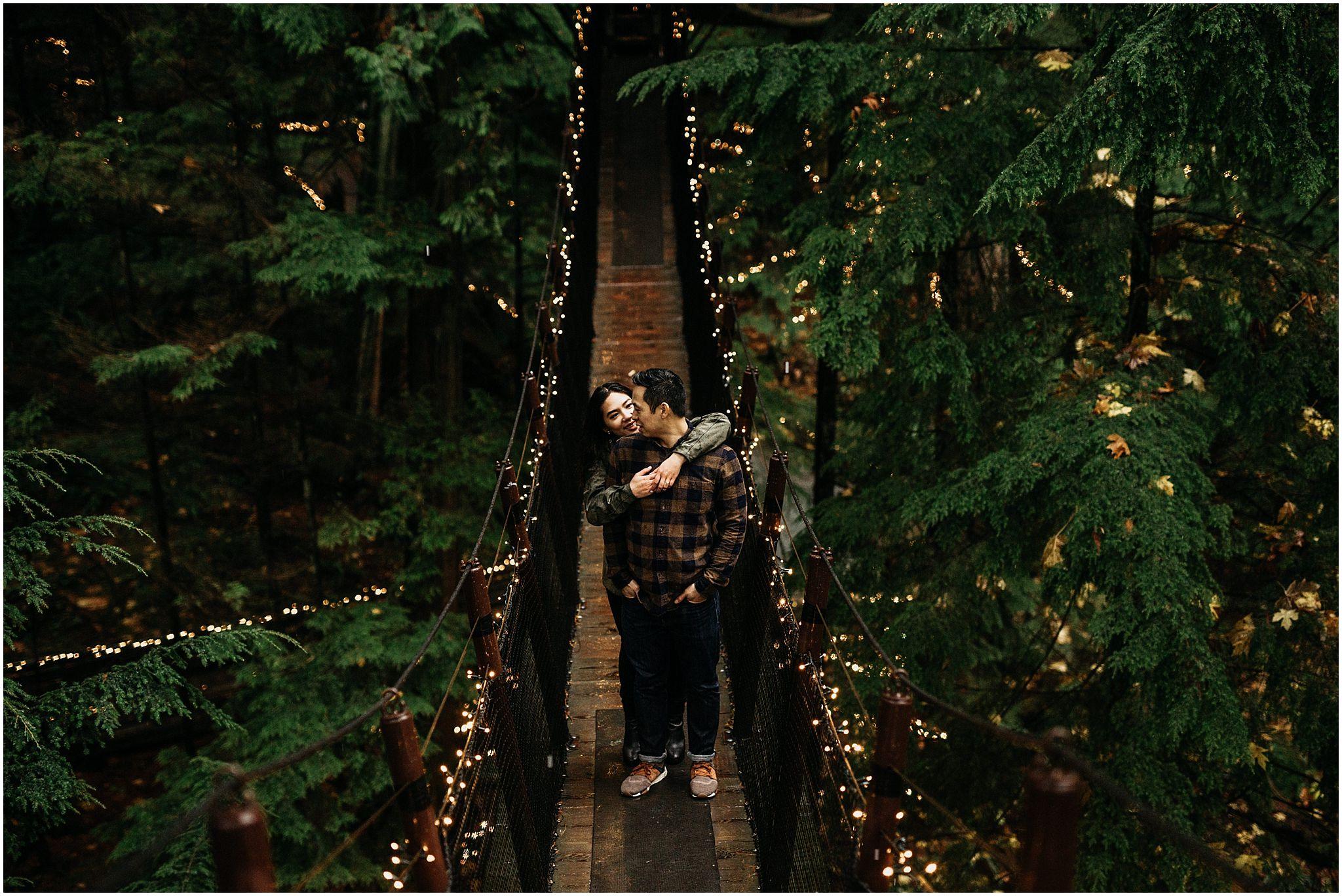 capilano suspension bridge canyon lights couple on bridge hugging