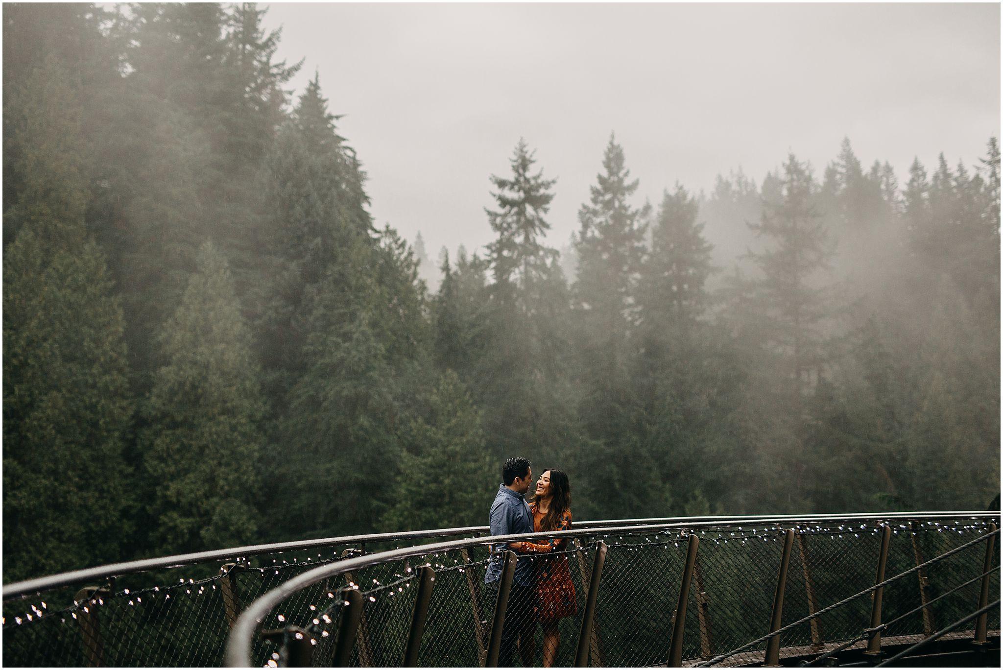 engaged couple on cliffwalk capilano suspension bridge fog rain trees