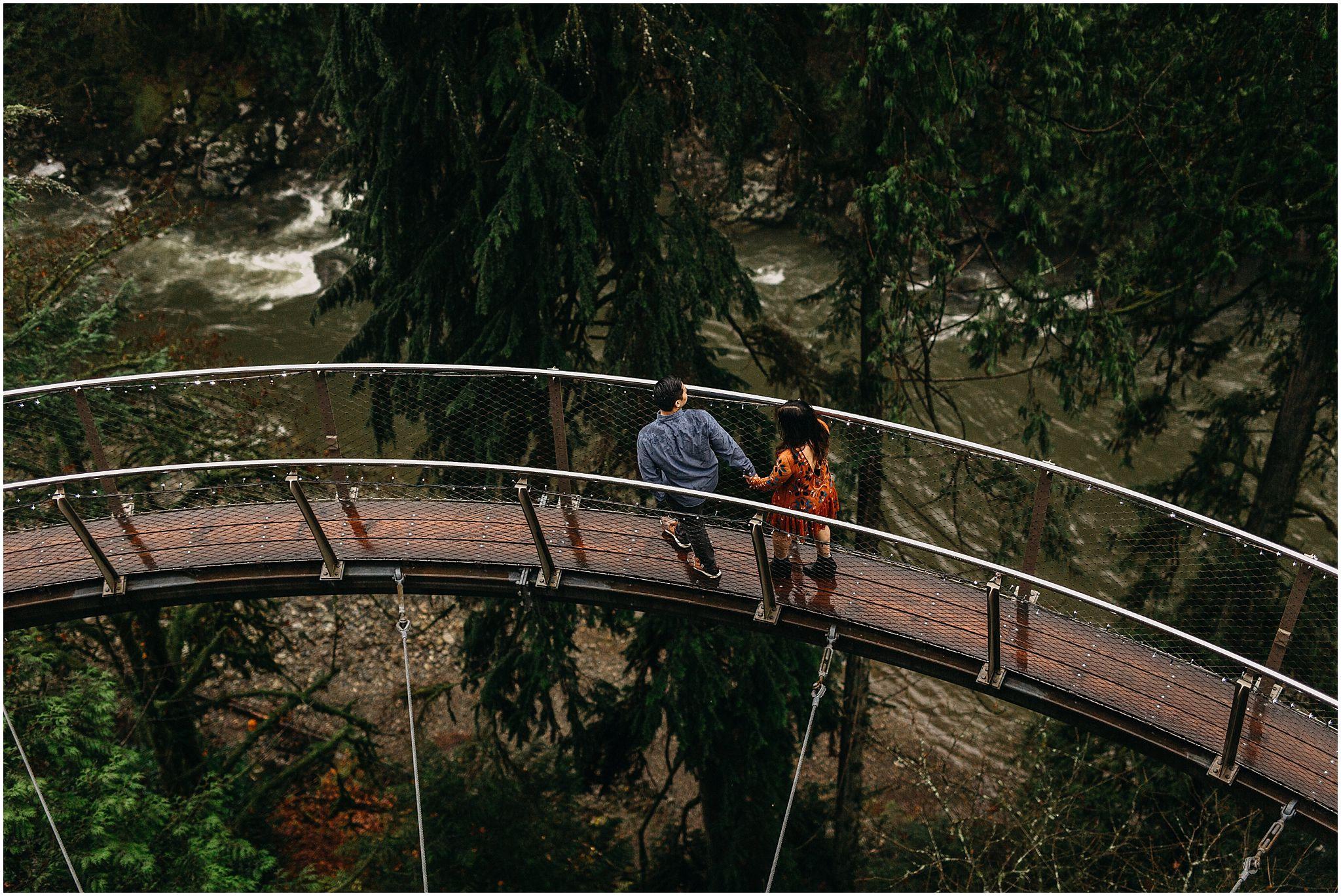 engaged couple holding hands walking along cliffwalk capilano suspension bridge