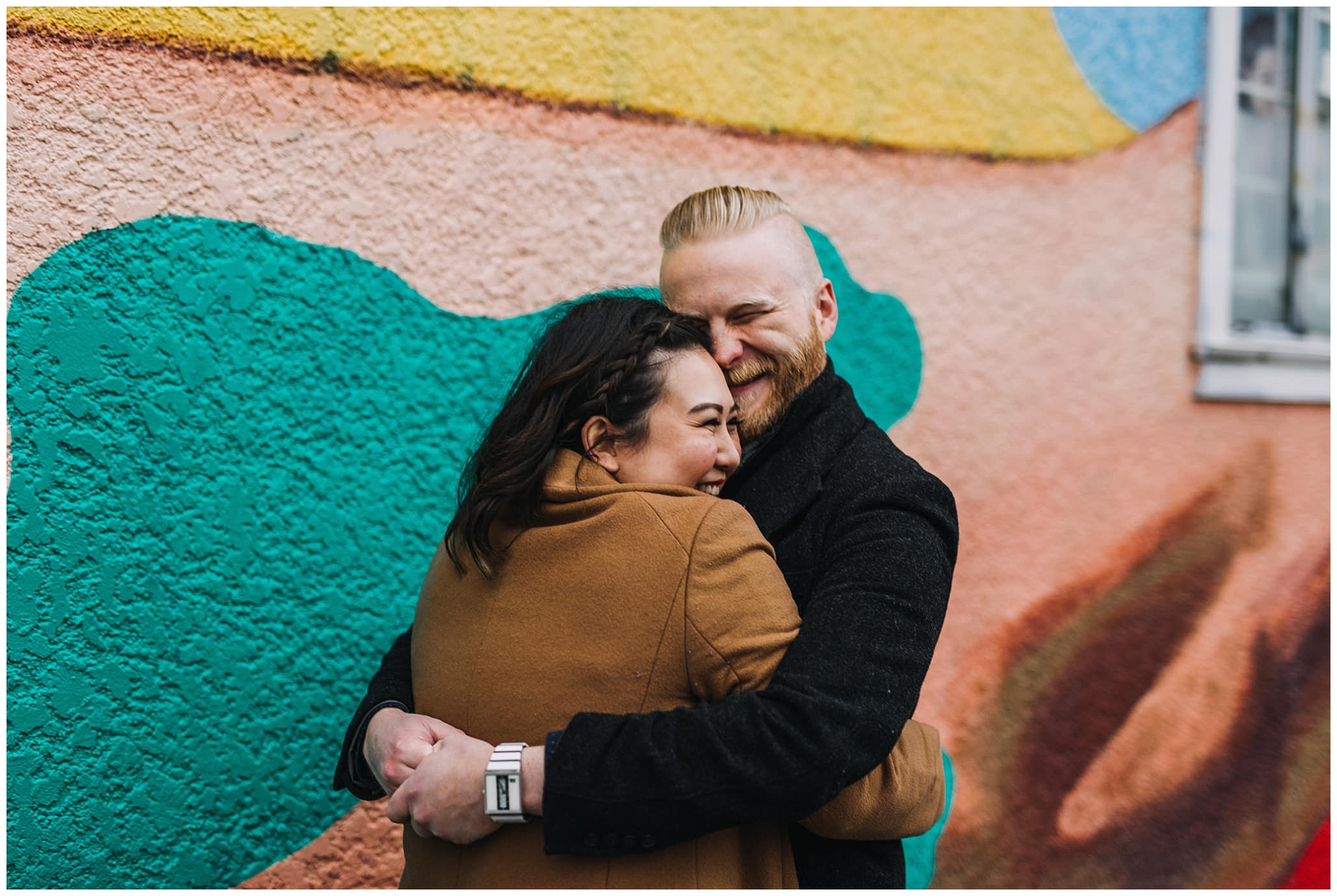 couple hugging at vancouver mural festival engagement photos