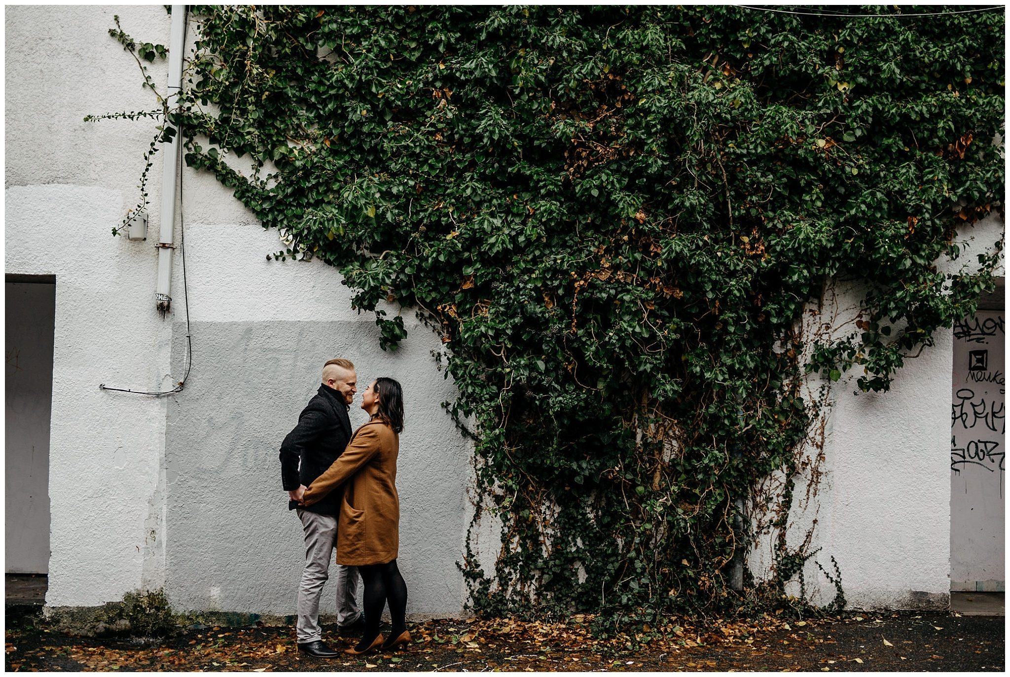 engaged couple holding hands vines on wall vancouver alley engagement