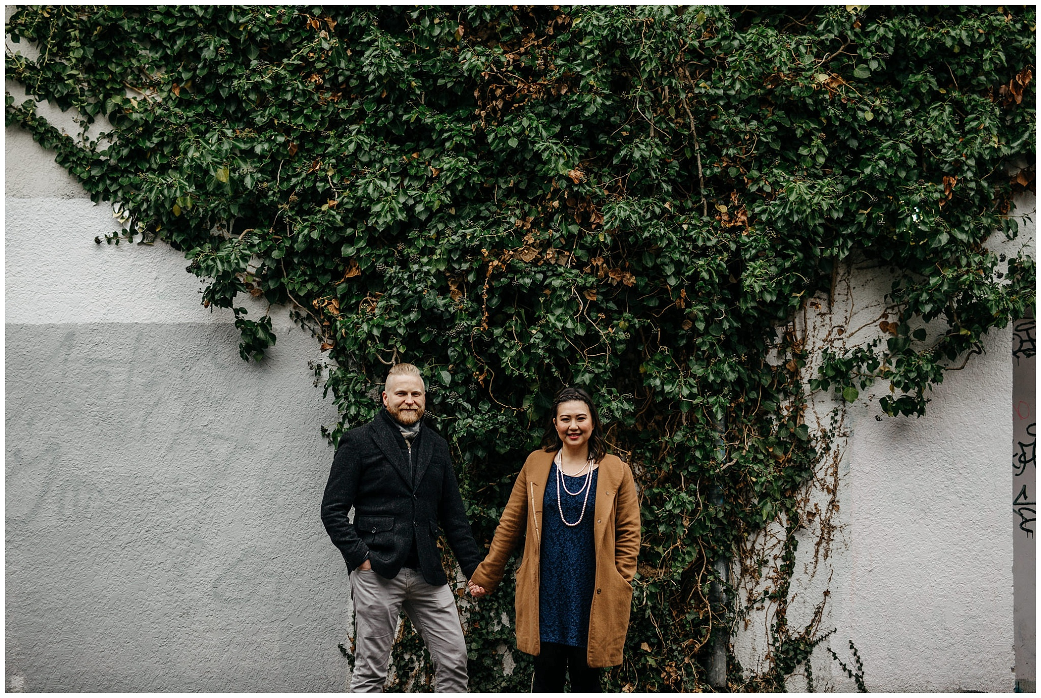 couple holding hands in front of ivy vines wall engagement vancouver