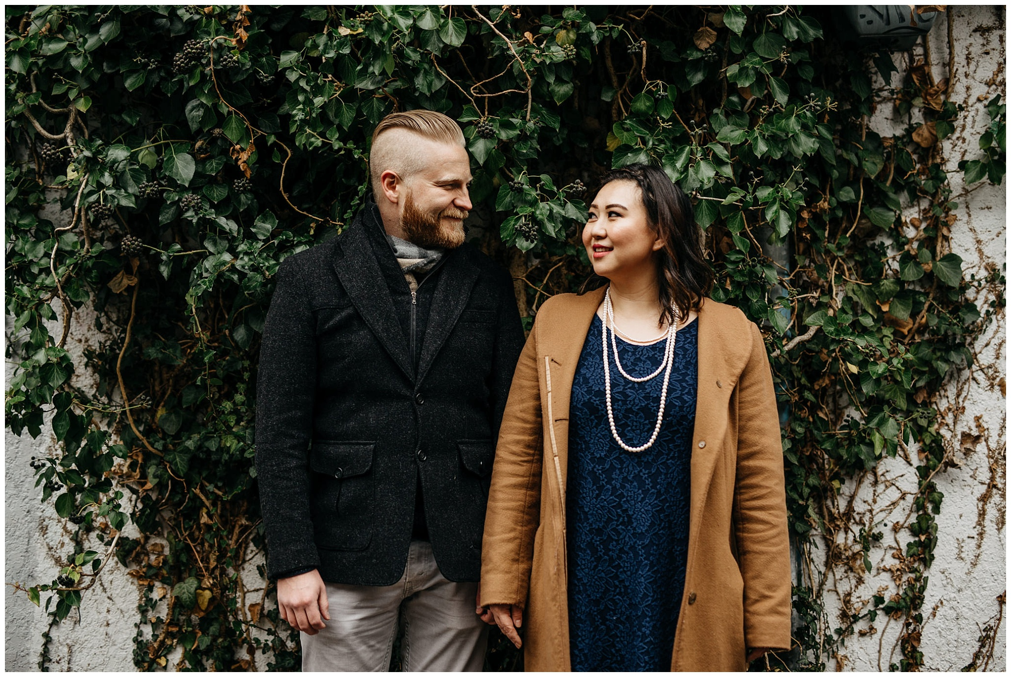 engaged couple holding hands in front of ivy vine wall vancouver