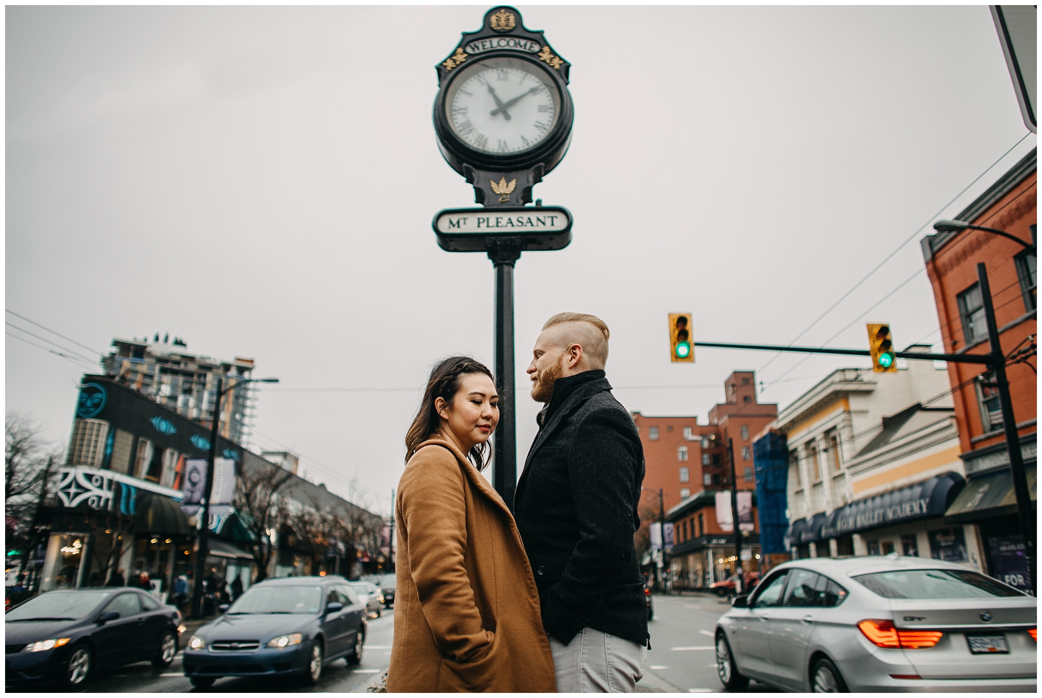 couple standing in front of mount pleasant clock vancouver city engagement