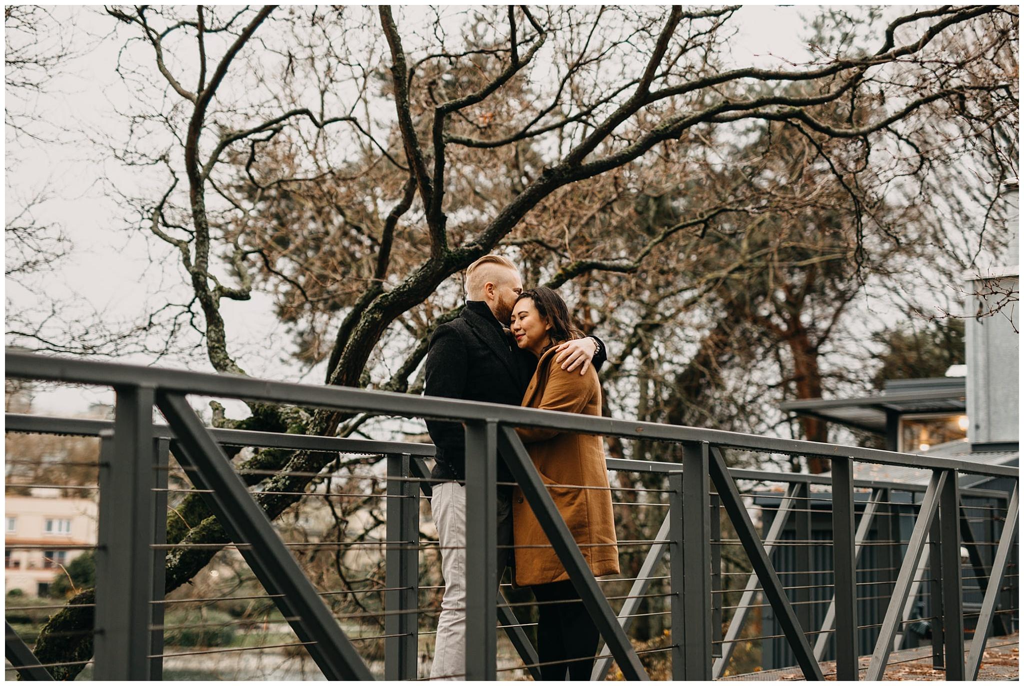 couple on bridge granville island winter trees engagement