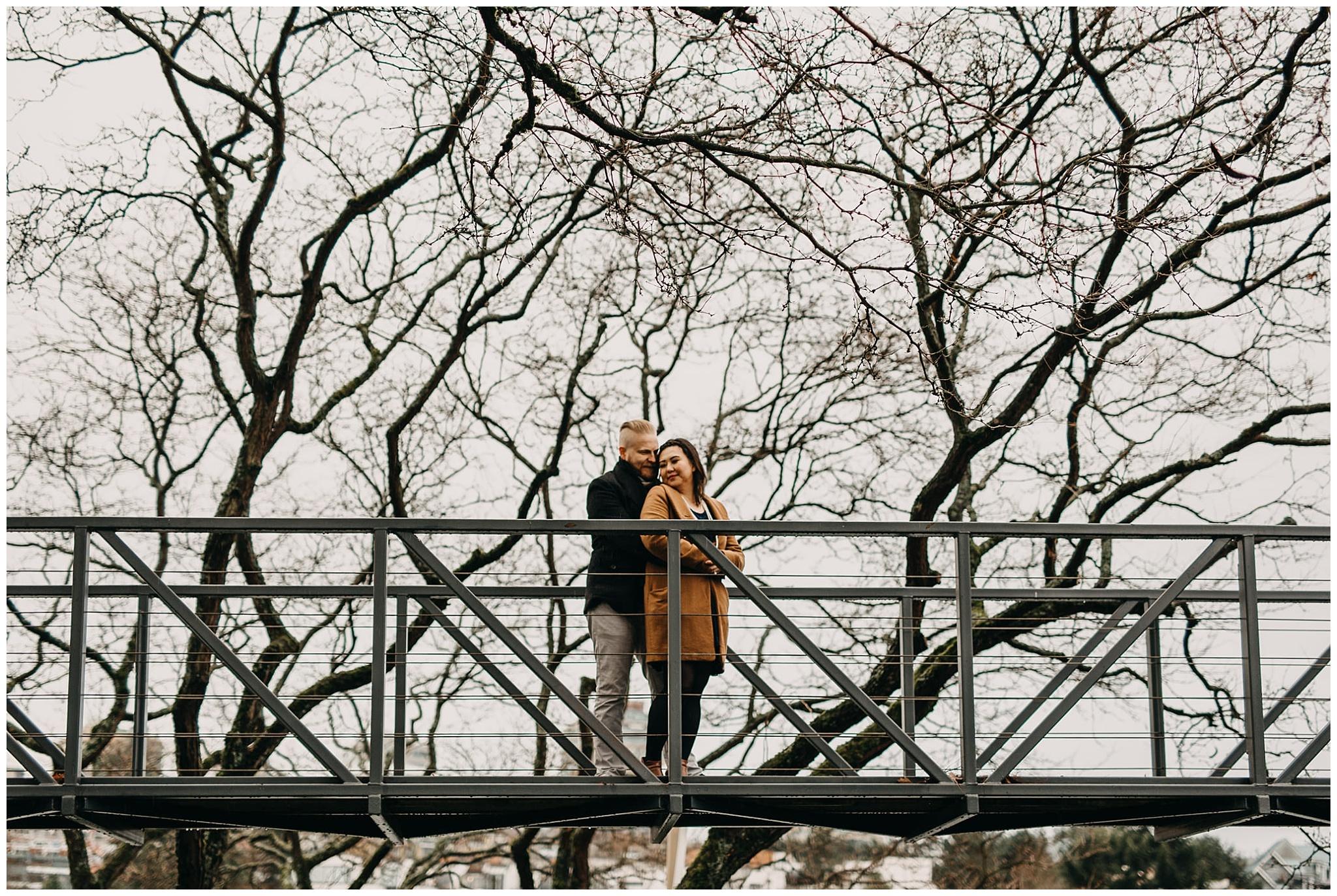 couple on bridge on granville island winter trees engagement