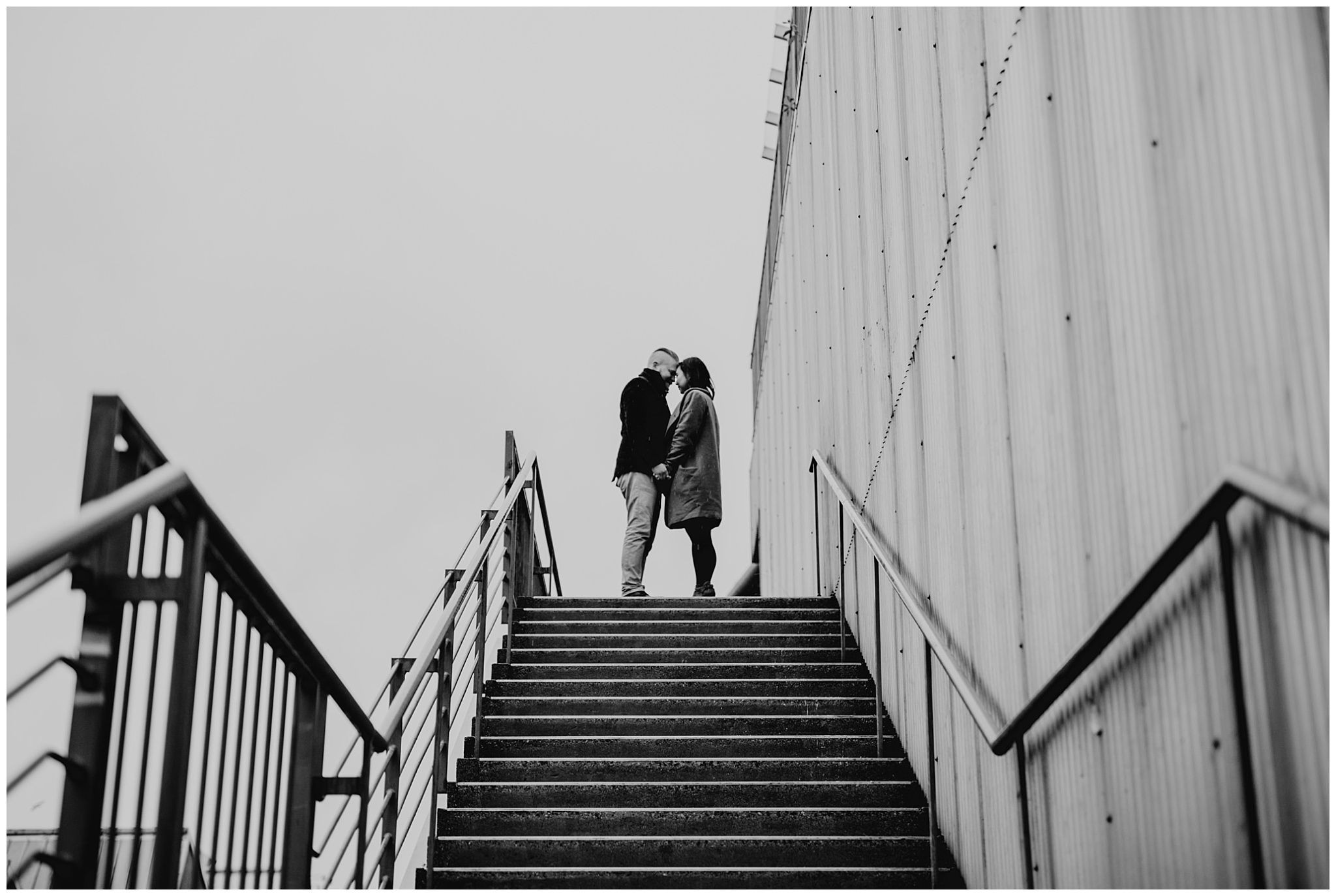couple at top of stairs granville island engagement vancouver urban city