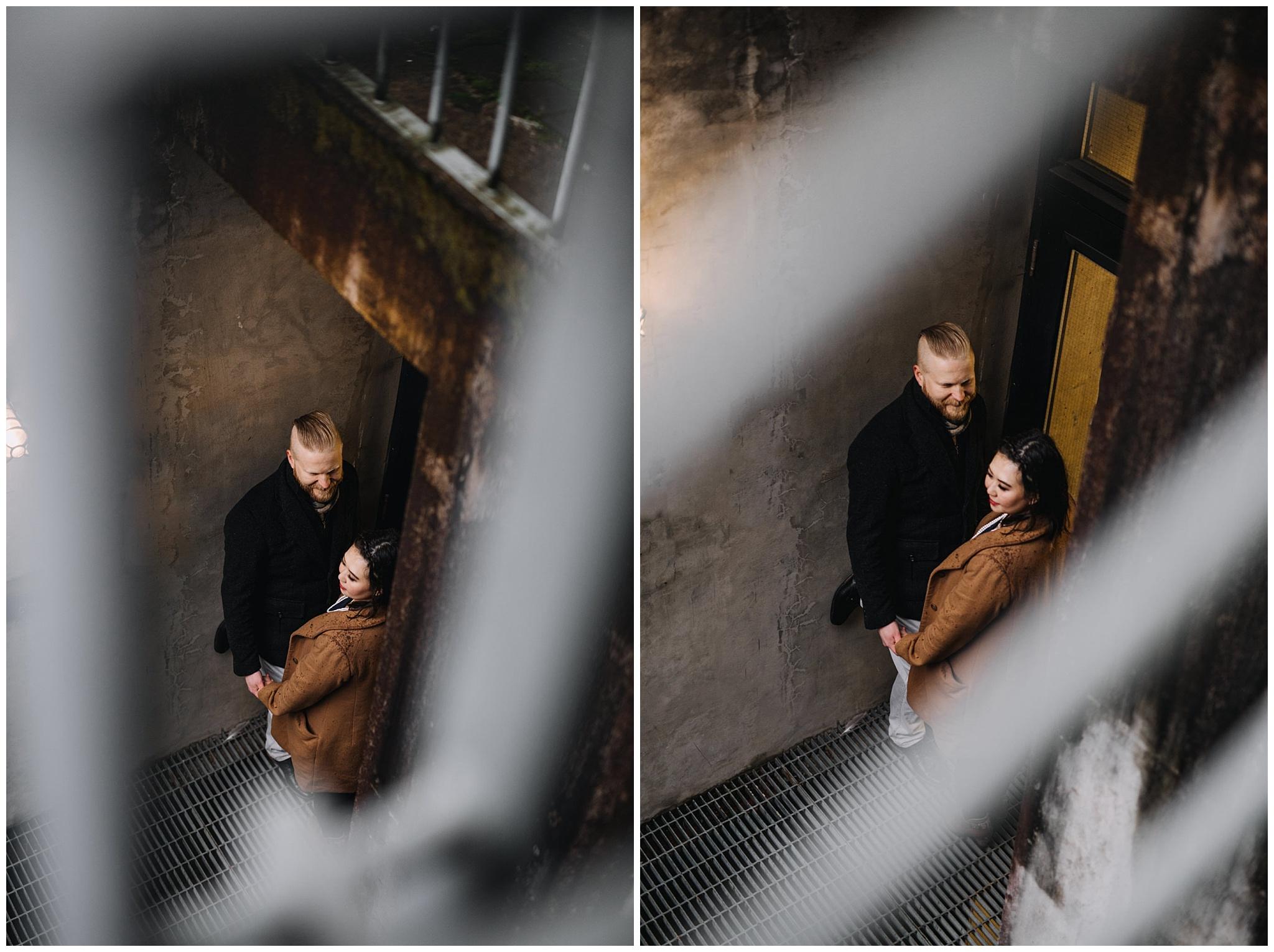 couple photographed through railings city urban engagement vancouver
