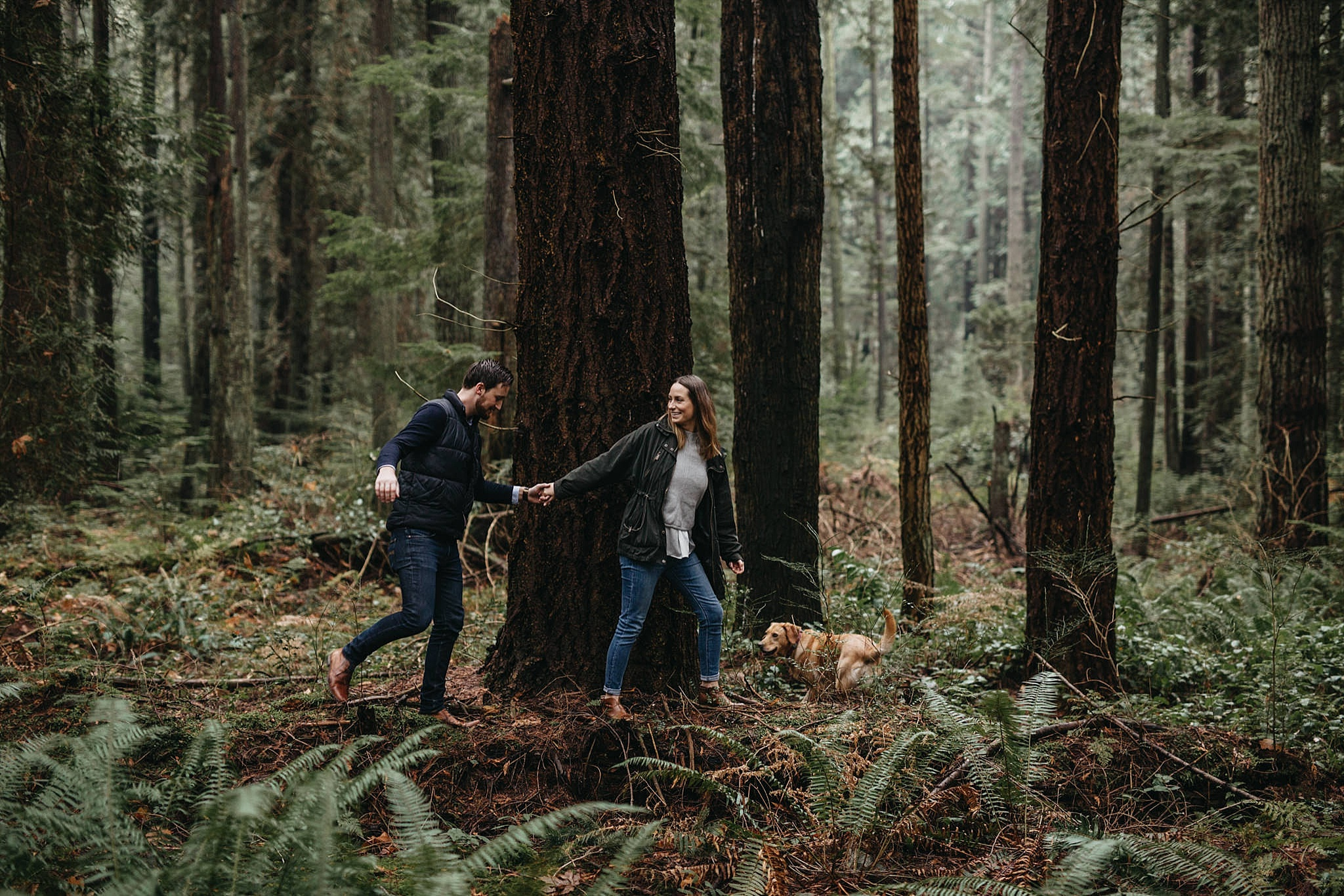 couple walking on log in forest pacific spirit park engagement