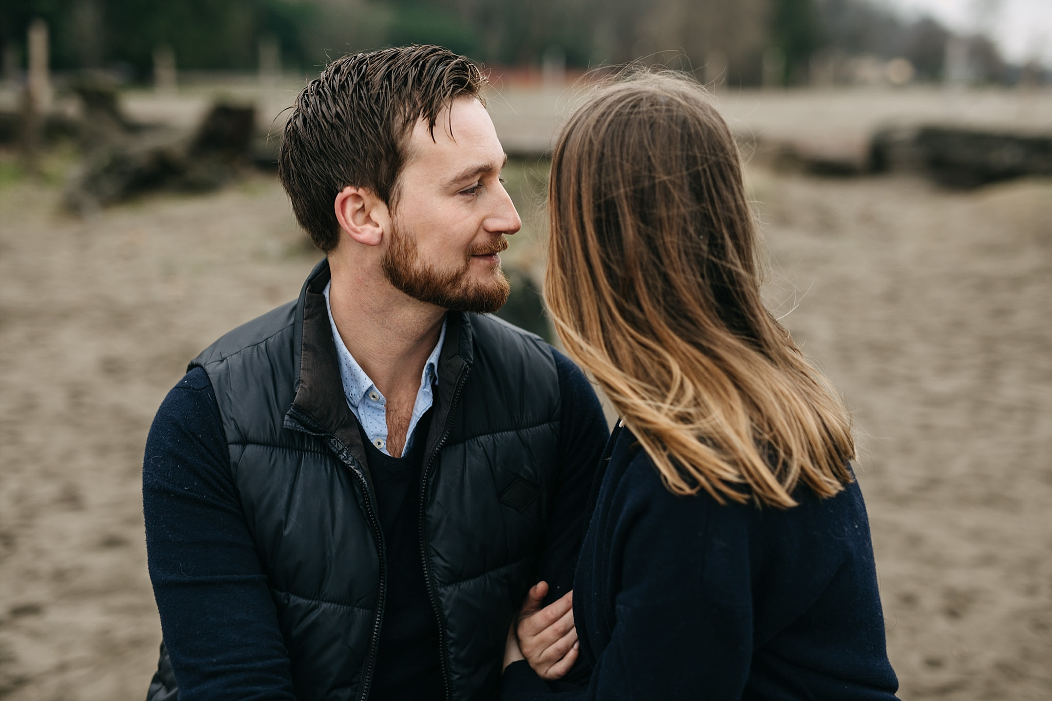 candid intimate moment between couple engagement spanish banks beach