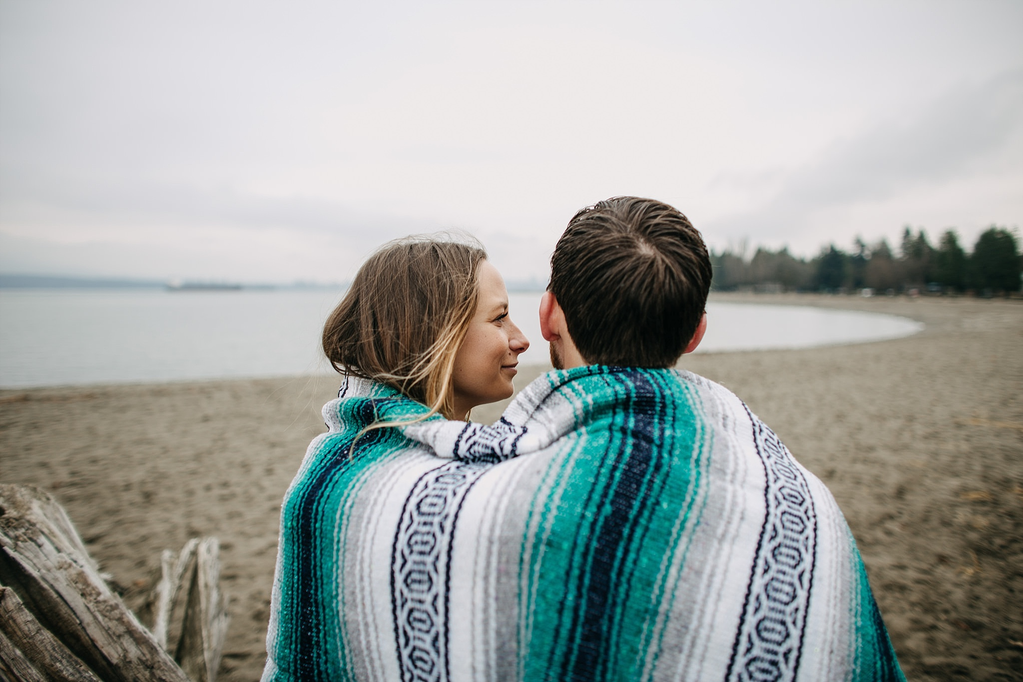 couple wrapped in blanket sitting on log at spanish banks beach engagement