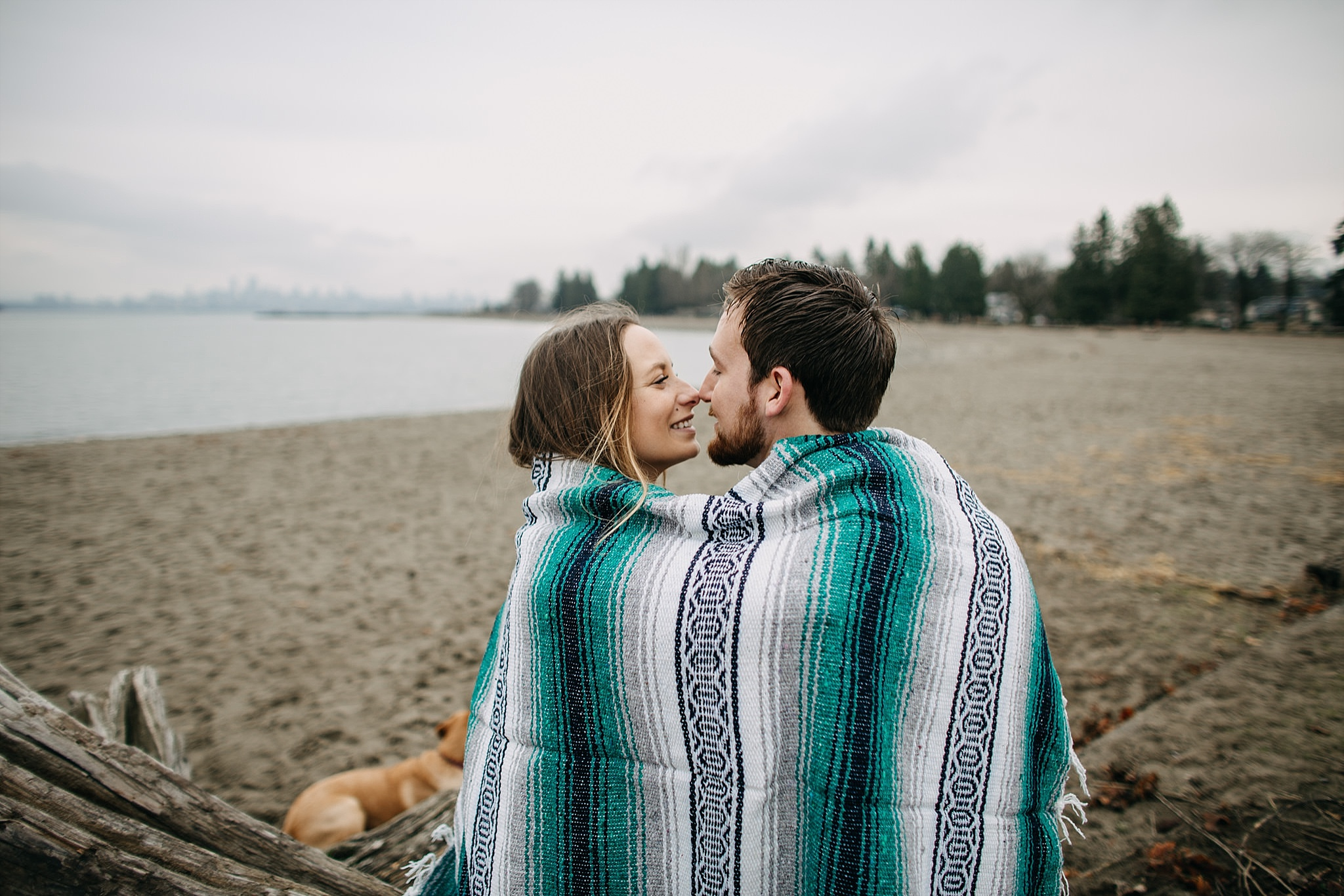 couple and puppy blanket beach spanish banks engagement