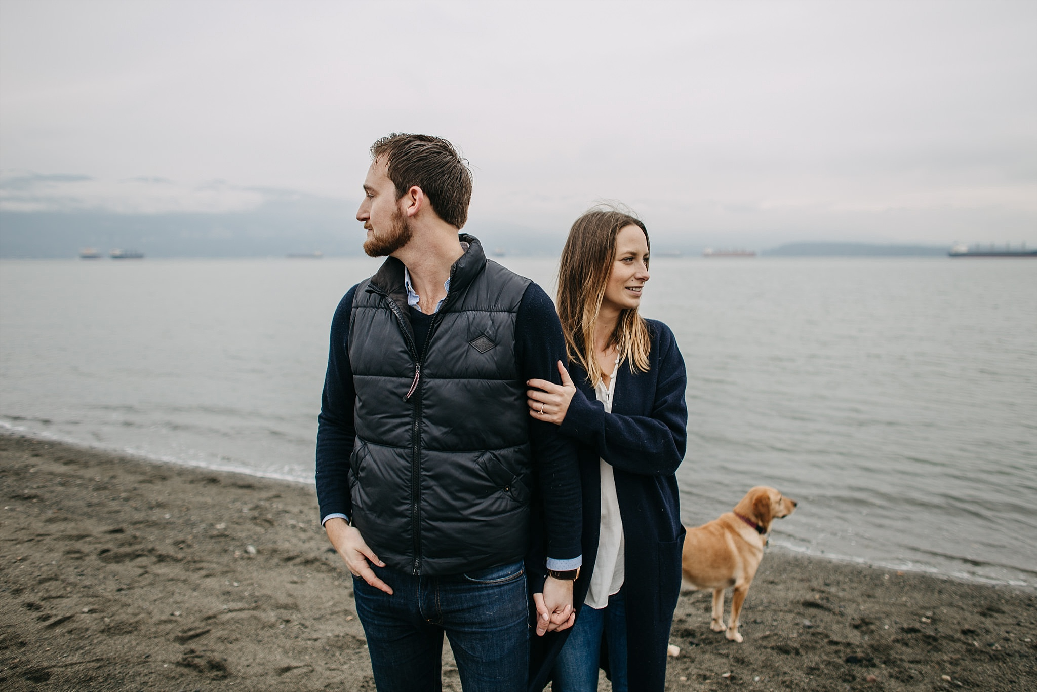couple with puppy on beach looking away spanish banks engagement