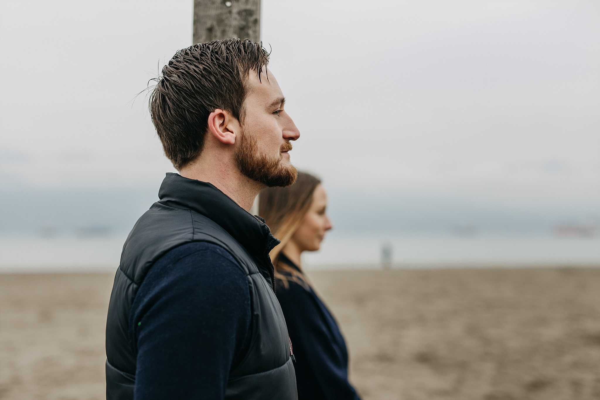 couple standing side by side on beach spanish banks engagement