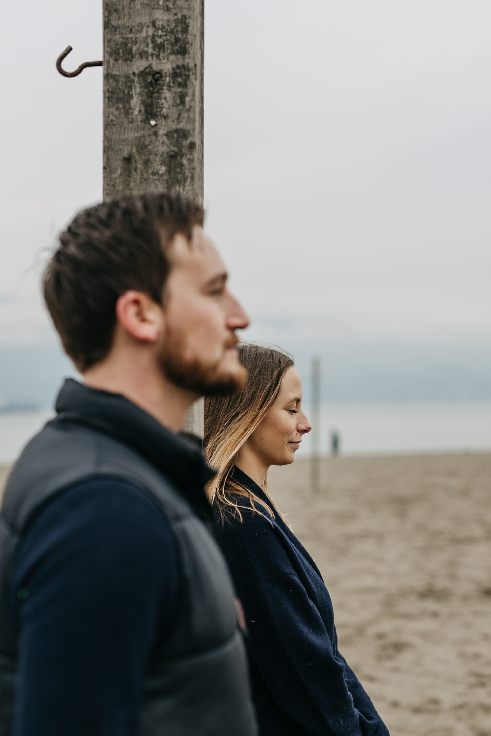 couple next to each other on beach spanish banks