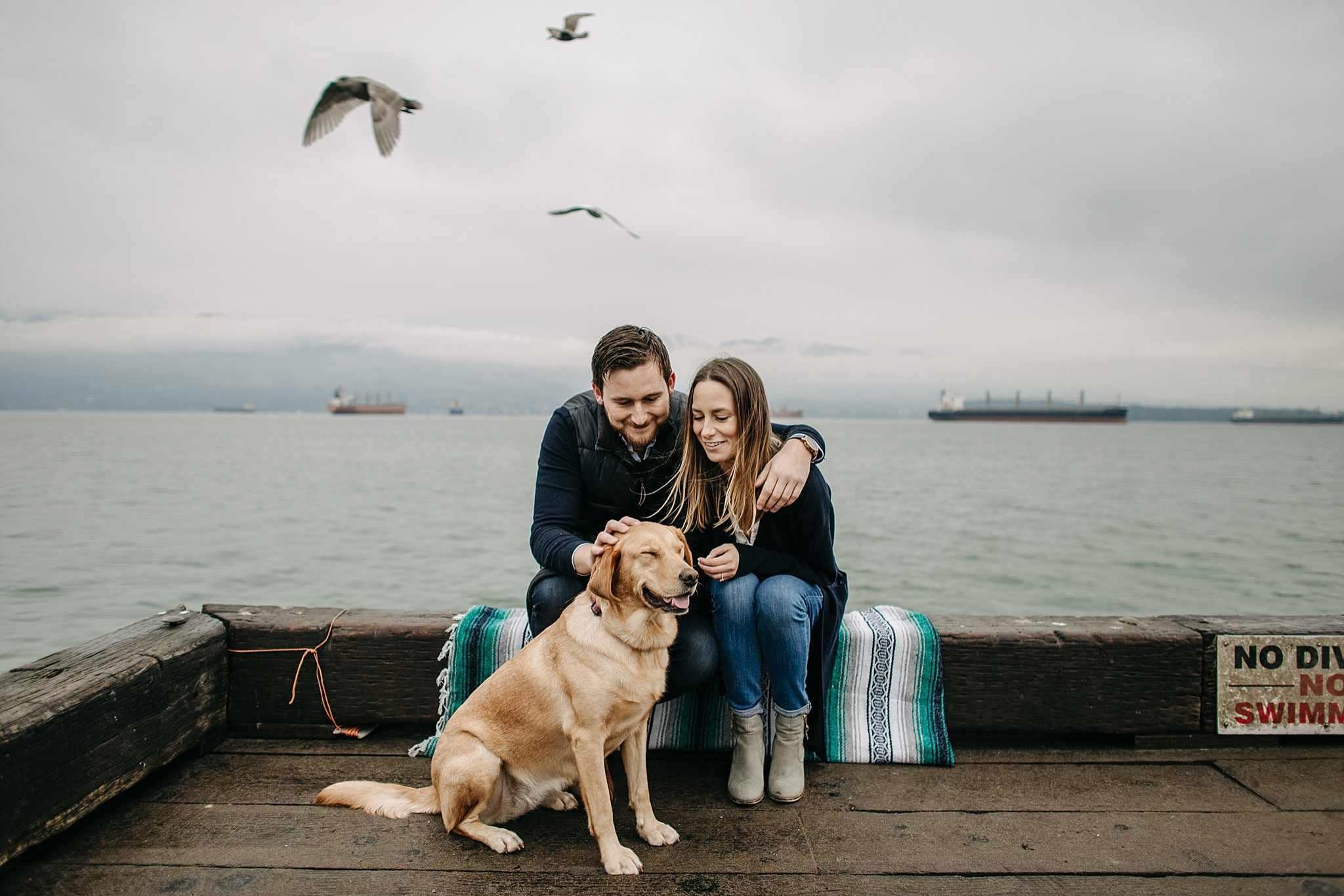 couple with puppy on dock birds flying spanish banks engagement