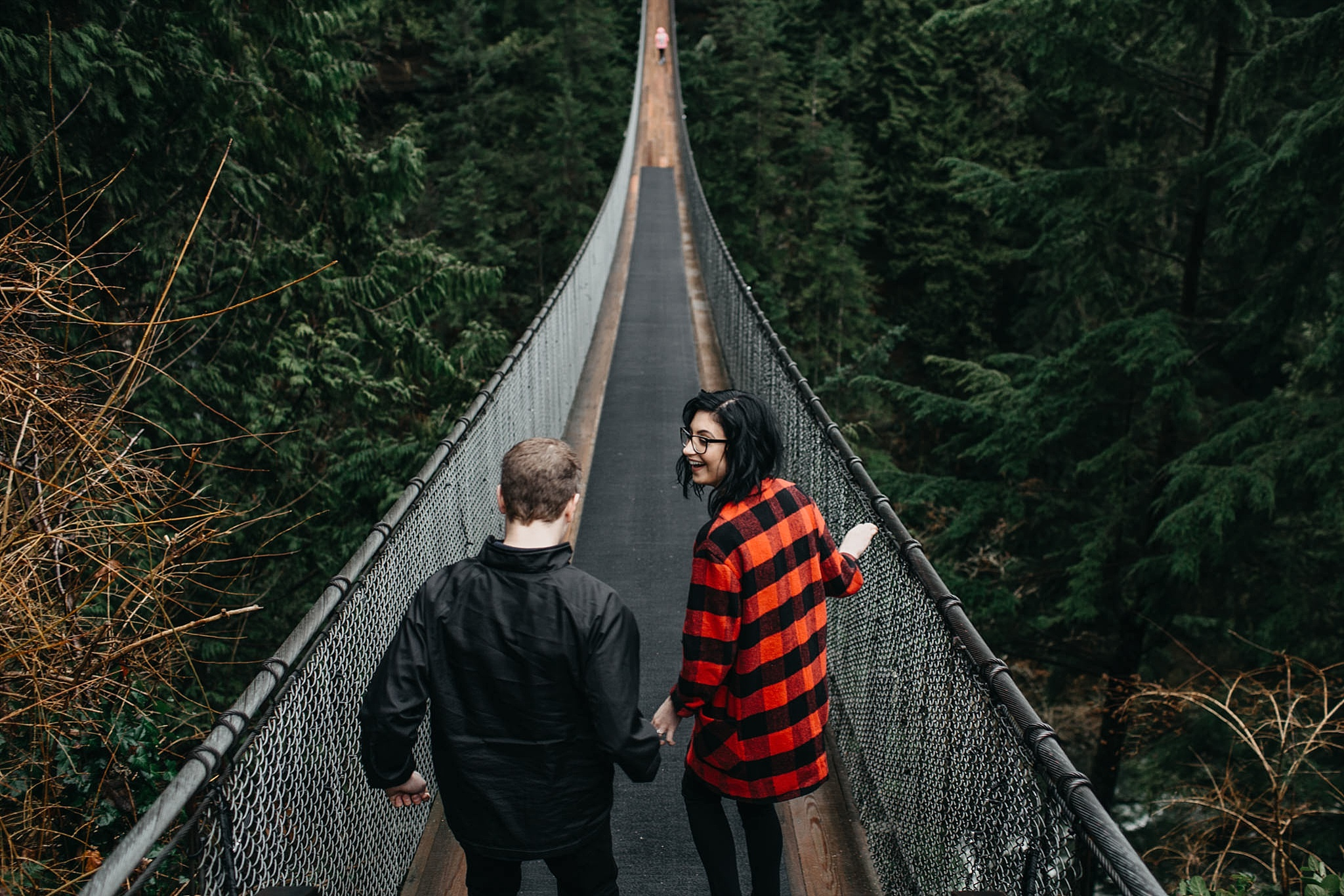 engaged couple walking on capilano suspension bridge holding hands